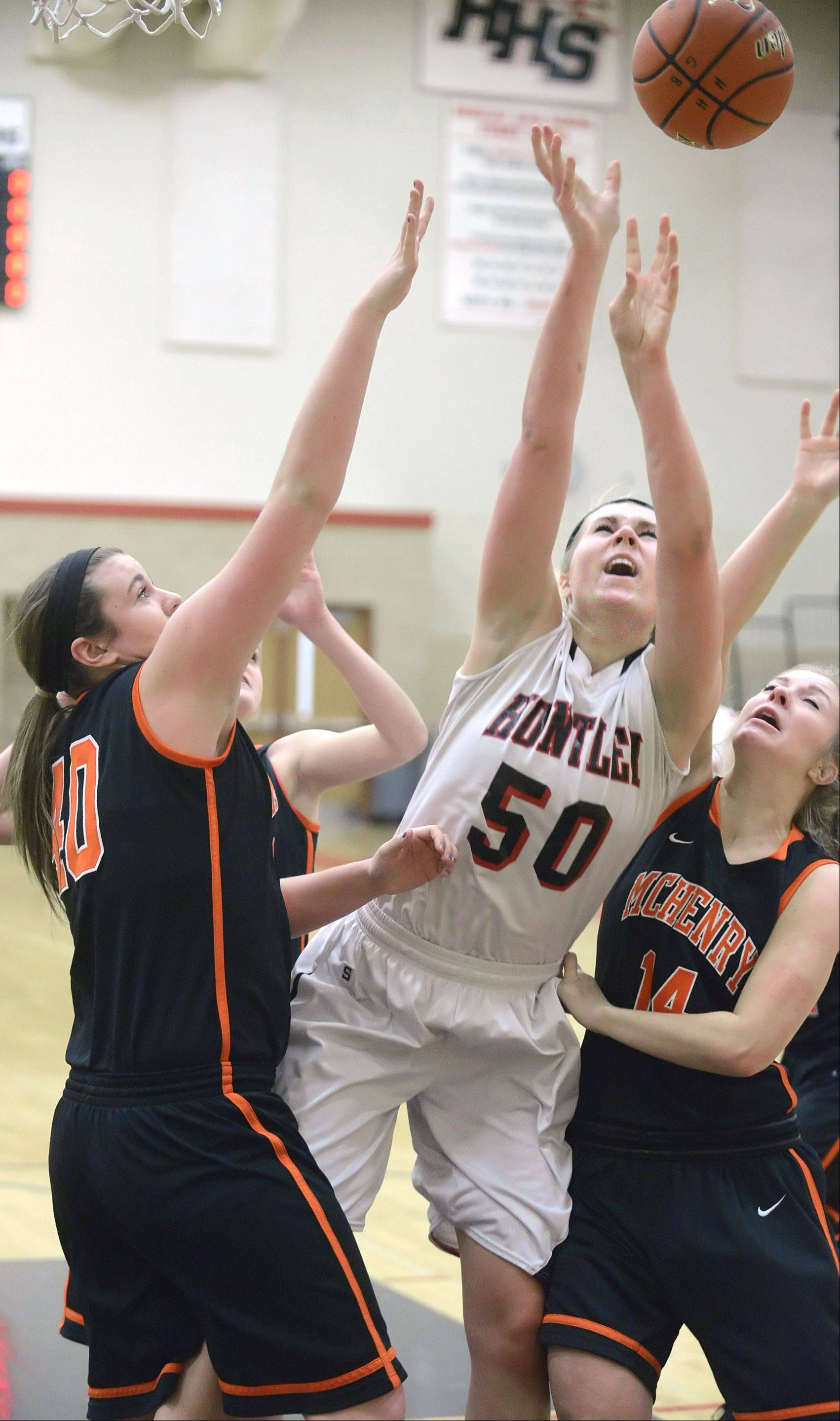 Huntley's Ali Andrews is swarmed by McHenry's Mckayla Snedeker, left, and Greta Taylor in the first quarter.
