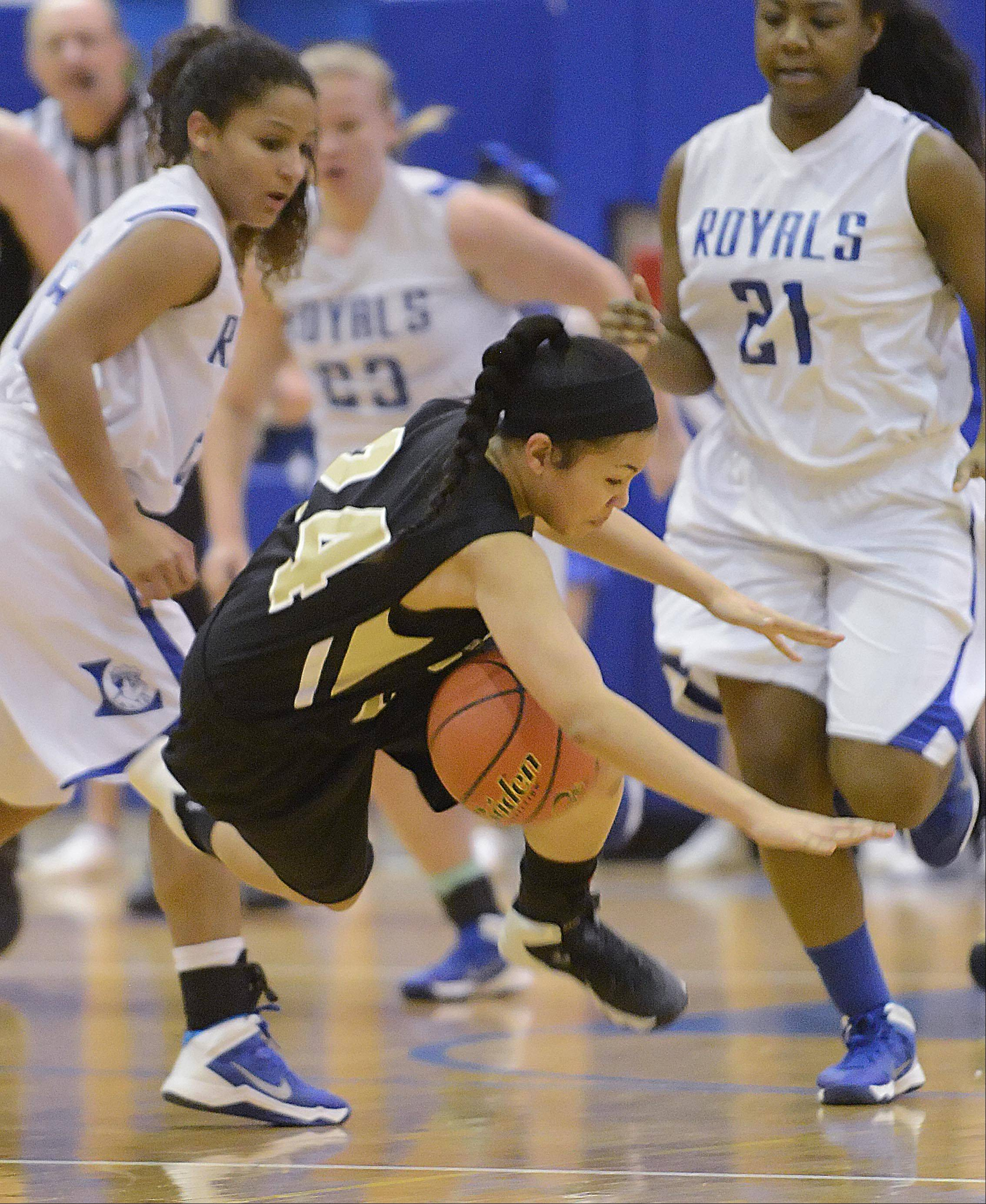 Streamwood's Kiana Jeremiah trips over the foot of Larkin's Victoria Patterson, left, Thursday in Elgin.