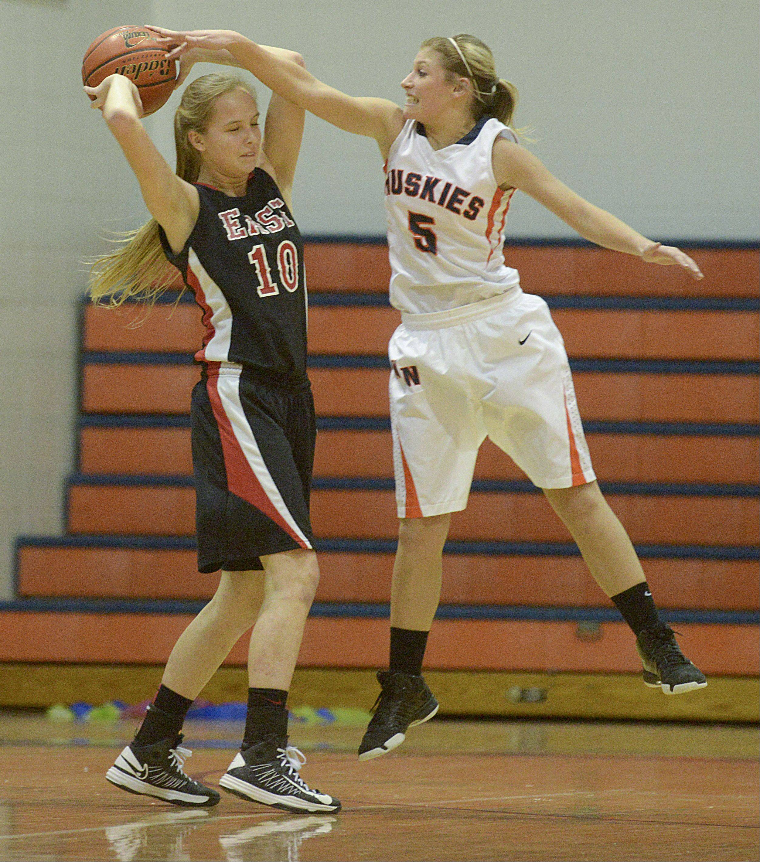 Glenbard East's Allison Hansen is guarded by Naperville North's Haley McClain.