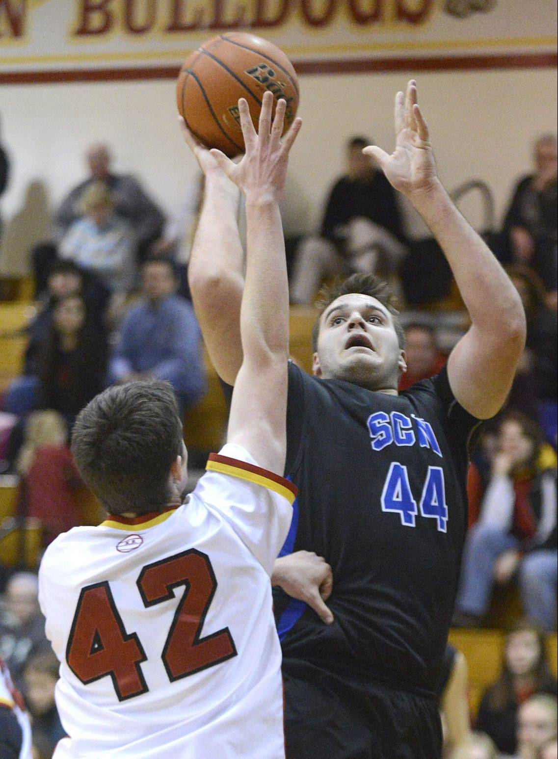 St. Charles North's Chase Gianacakos shoots over Batavia's Ryan Olson in the second quarter on Friday in Batavia.