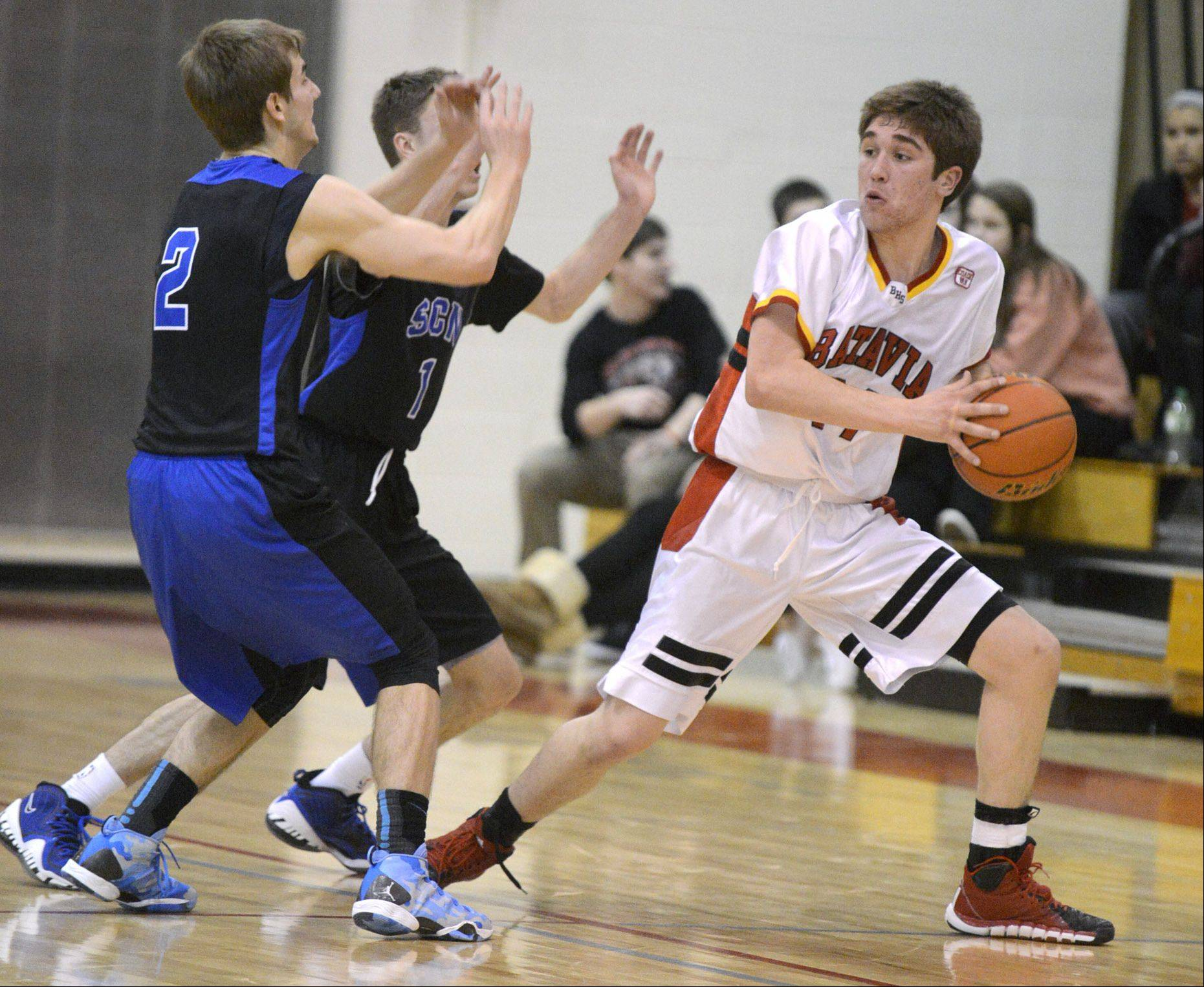 St. Charles North's Jake Ludwig (2) and Alec Goetz (1) swarm Batavia's Tyler Lovestrand in the second quarter on Friday.