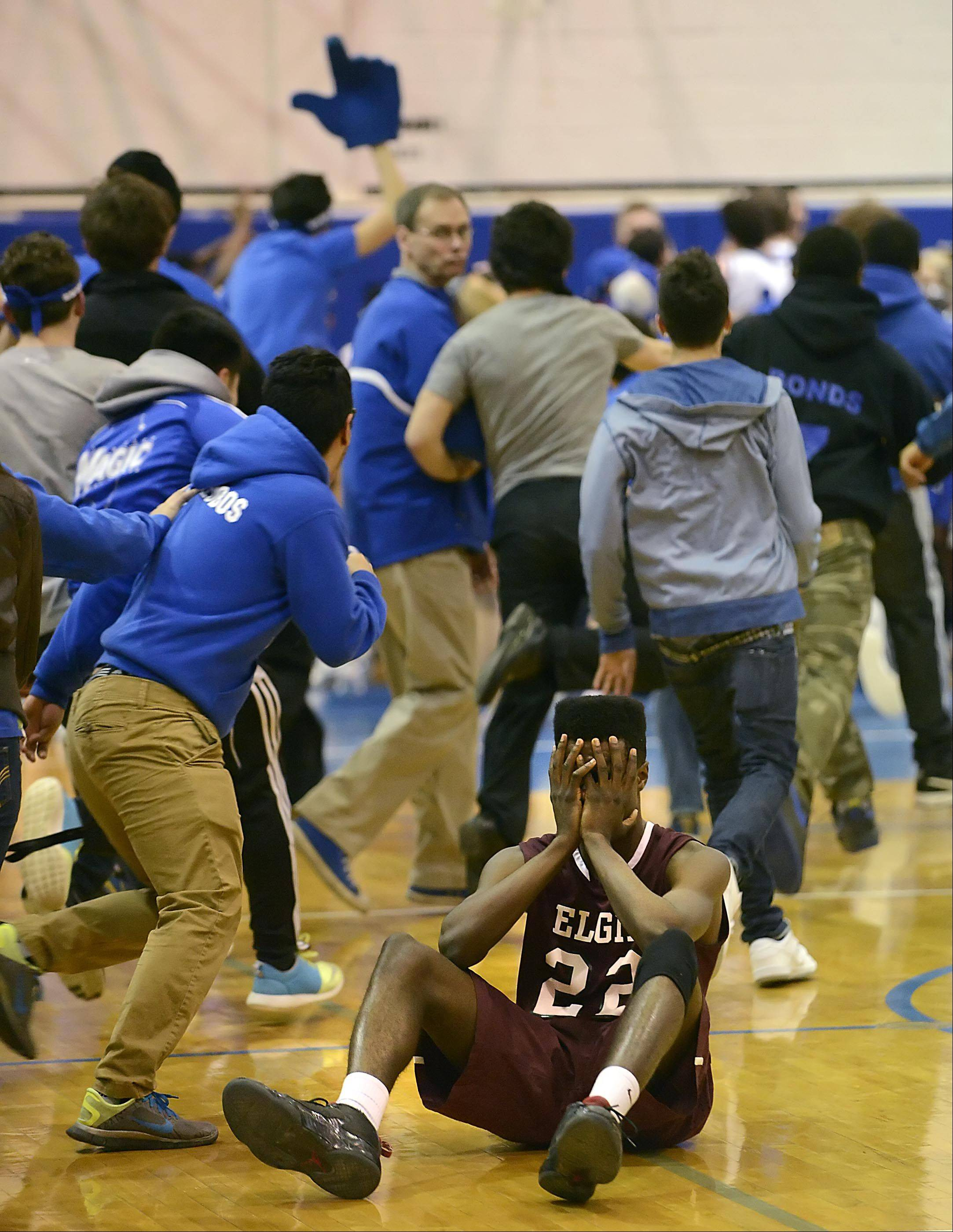 Elgin's Desmond Sanders covers his face as Larkin students rush the floor as the Royals beat the Maroons in the final seconds Friday at Larkin High School in Elgin.