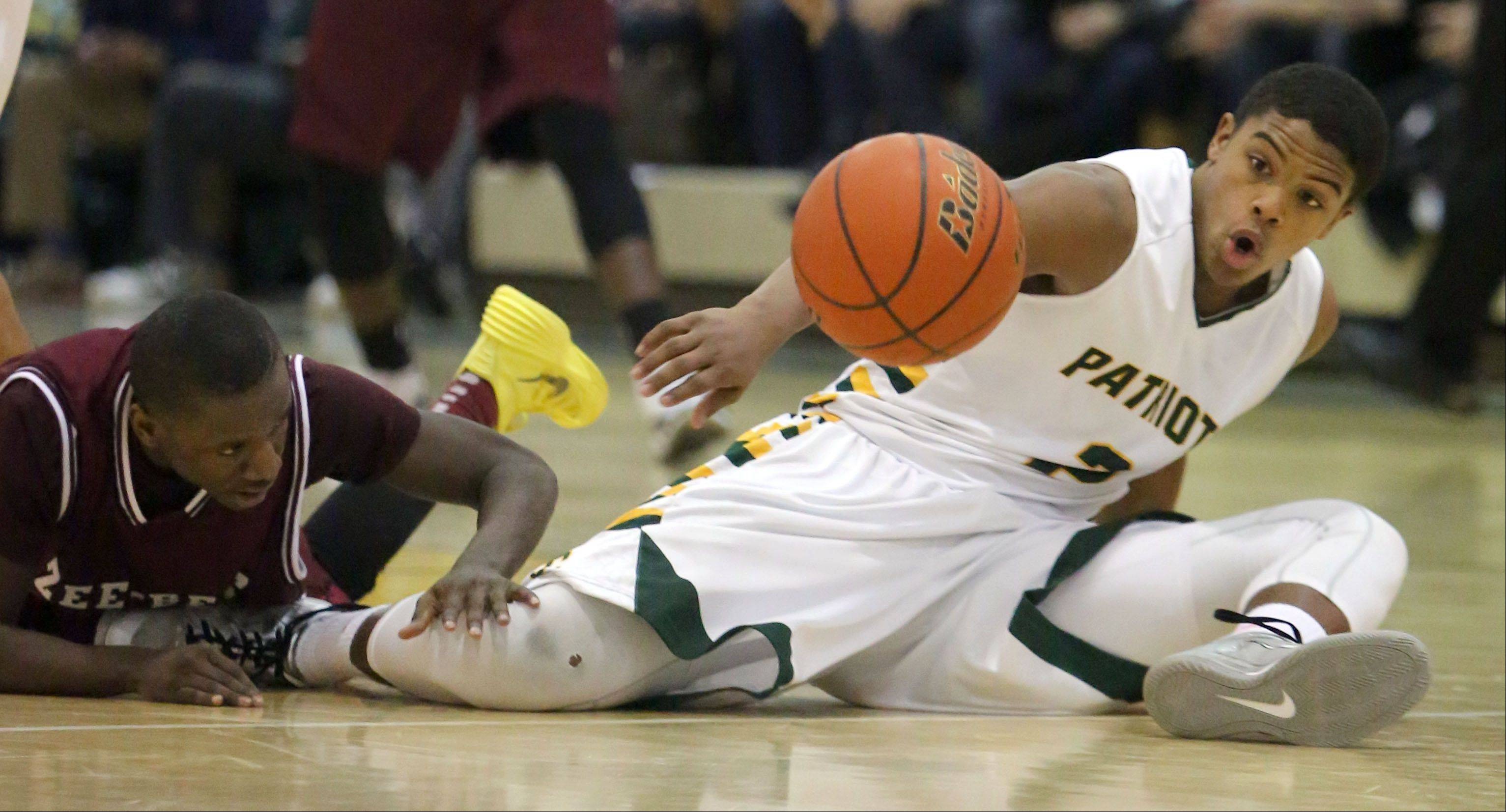 Stevenson's Cameron Green, right, and Zion-Benton's Maurice Young hit the floor in pursuit of a loose ball during NSC Lake play Friday night at Stevenson.