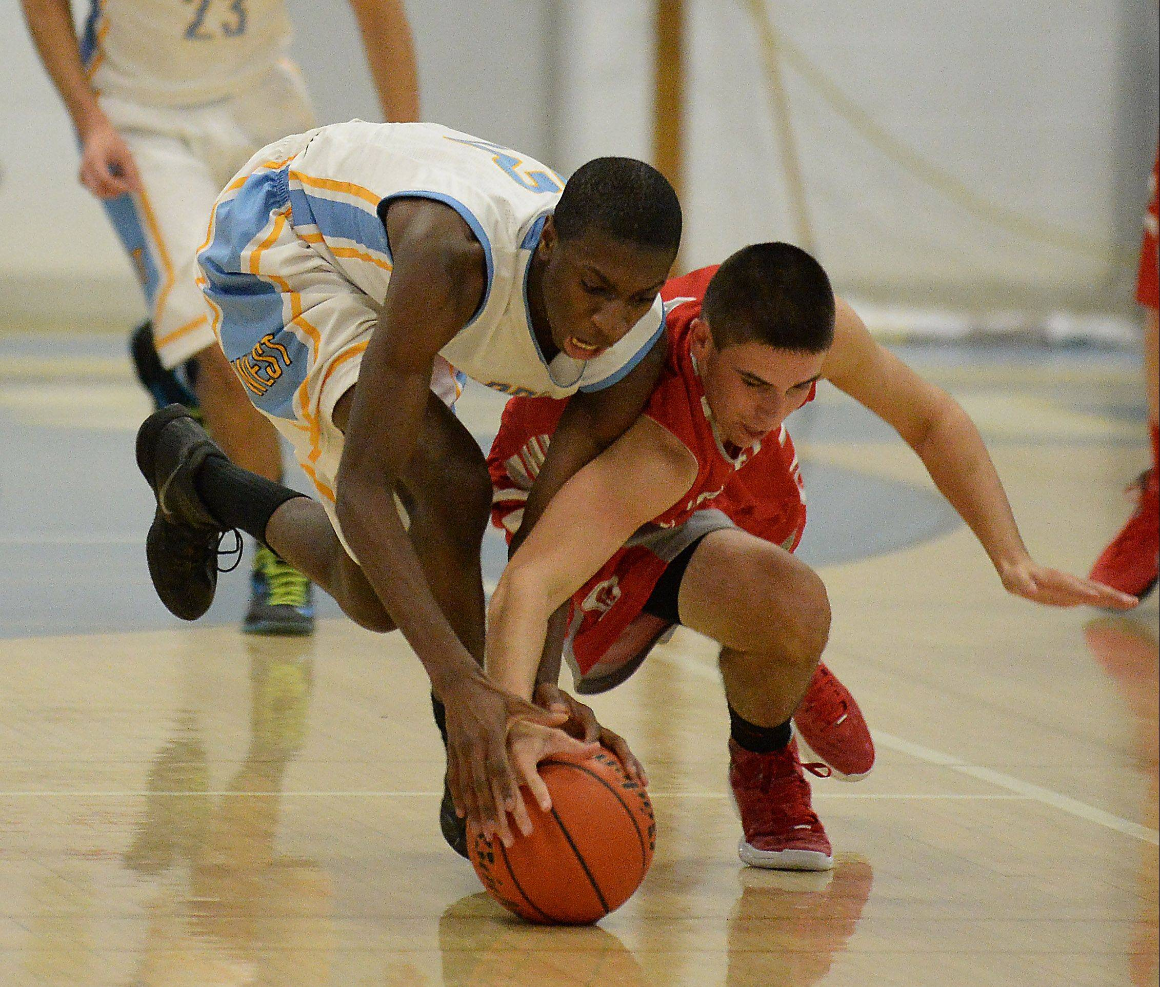 Maine West's Josh Redd (13) and Deerfield's Eric Porter (3) fight for a loose ball during CSL North play Friday at Maine West.