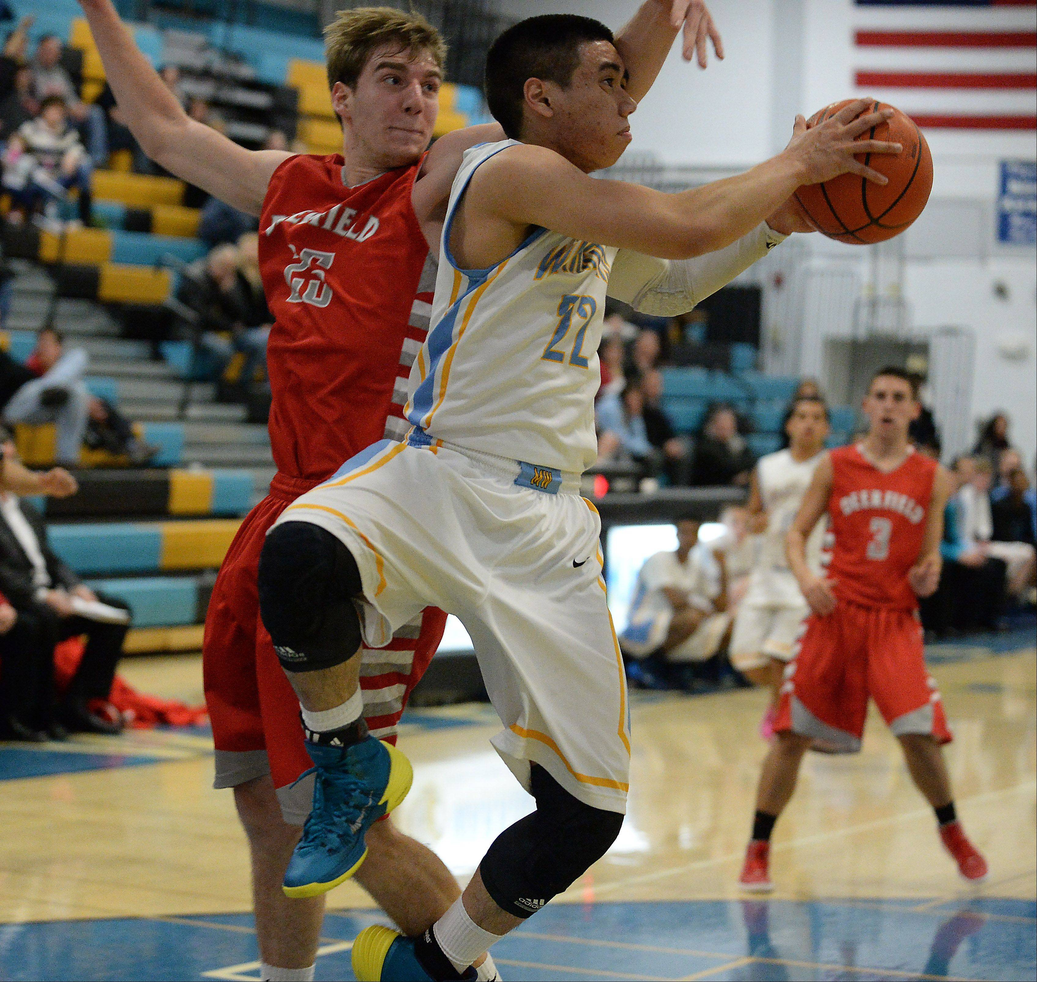 Maine West's Joel Ferraren (22) goes to the basket as Deerfield's Stefanos Fasianos (25) attempts to block his path on Friday at Maine West.