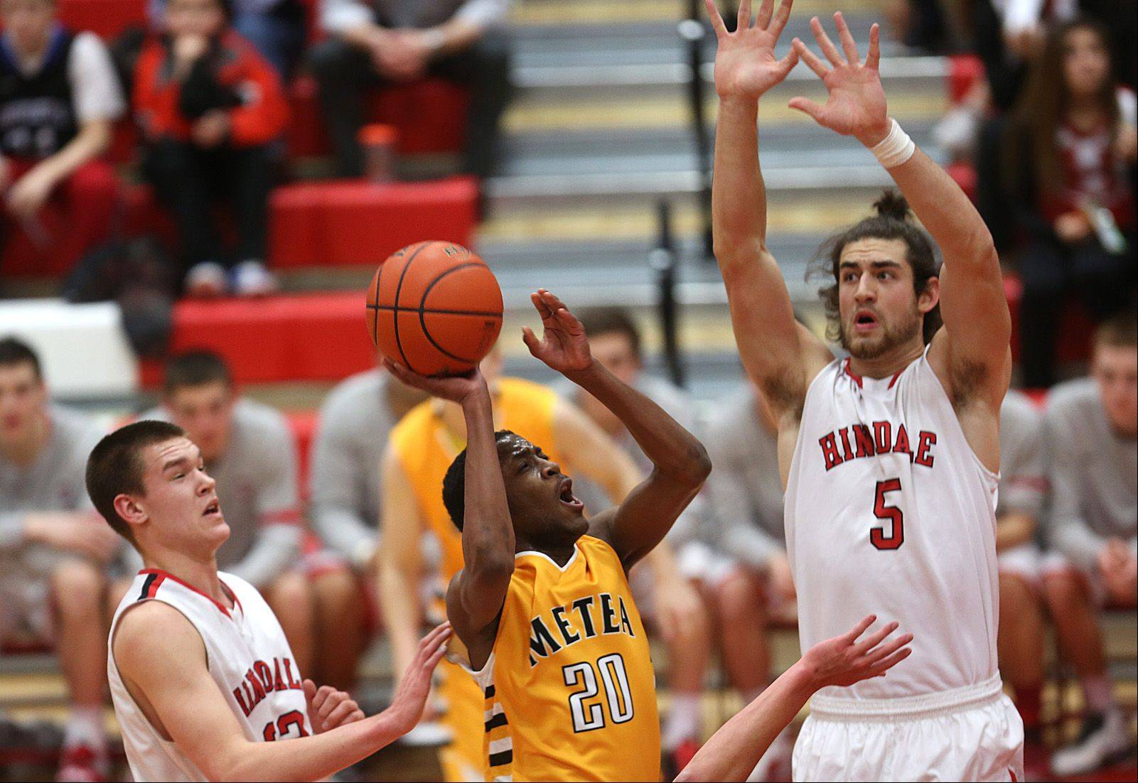 Metea Valley's Marquell Oliver drives between the Hinsdale Central defense of Matt Rafferty, left, and Ian Bunting, right.
