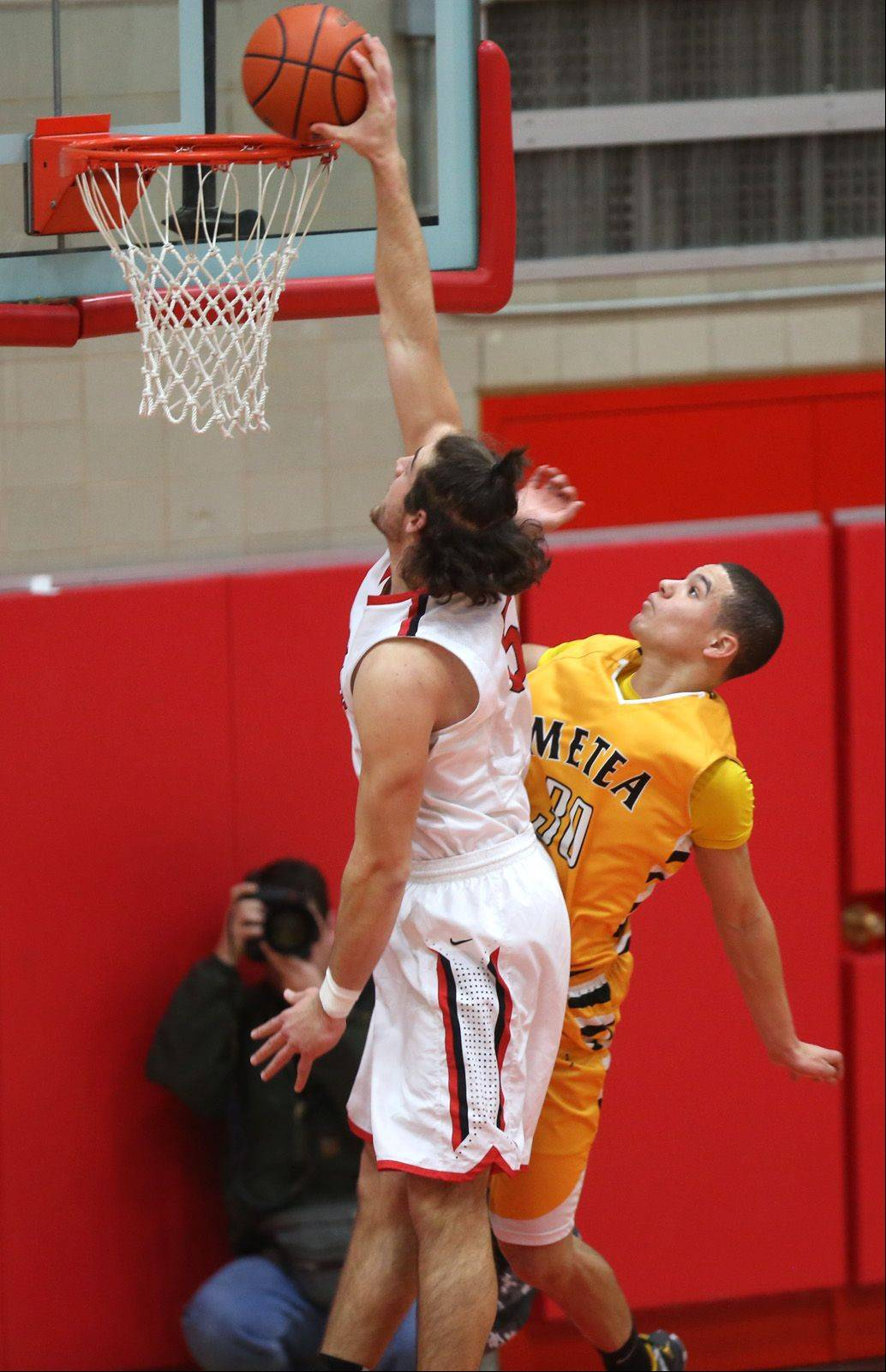 Hinsdale Central's Ian Bunting jams over Metea Valley's Nick Dodson, right.