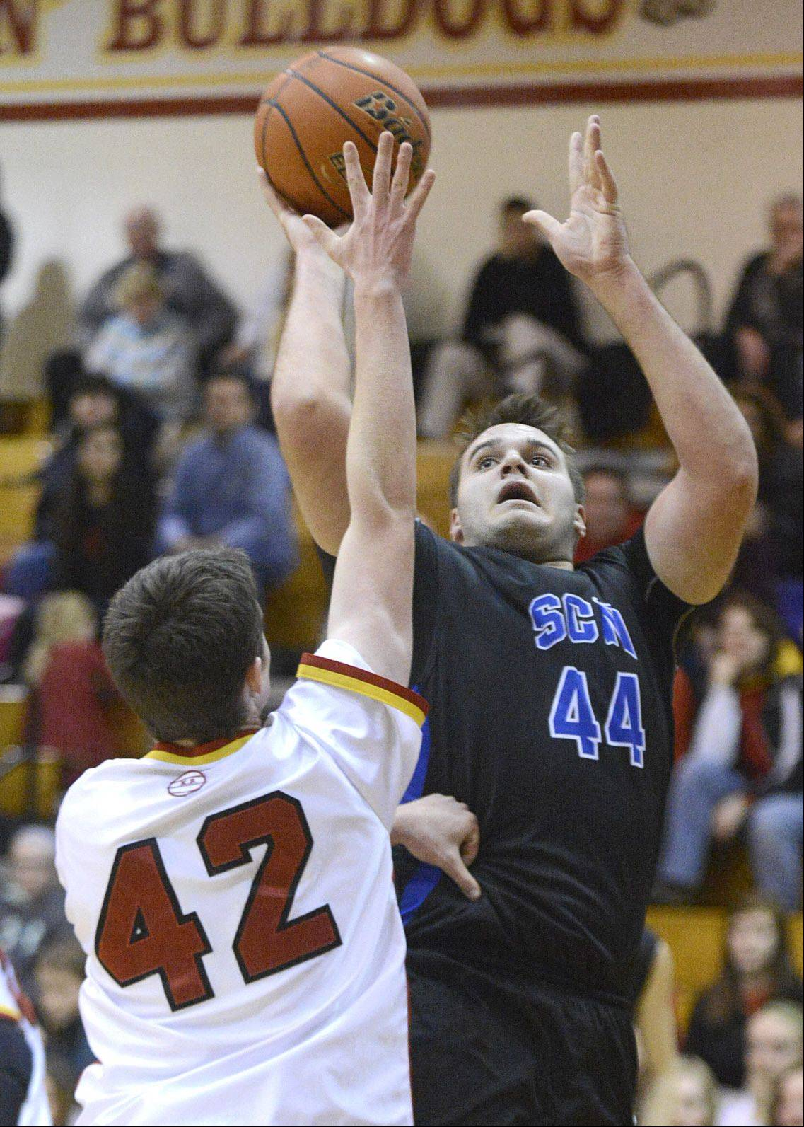 St. Charles North's Chase Gianacakos shoots over a block by Batavia's Ryan Olson in the second quarter.