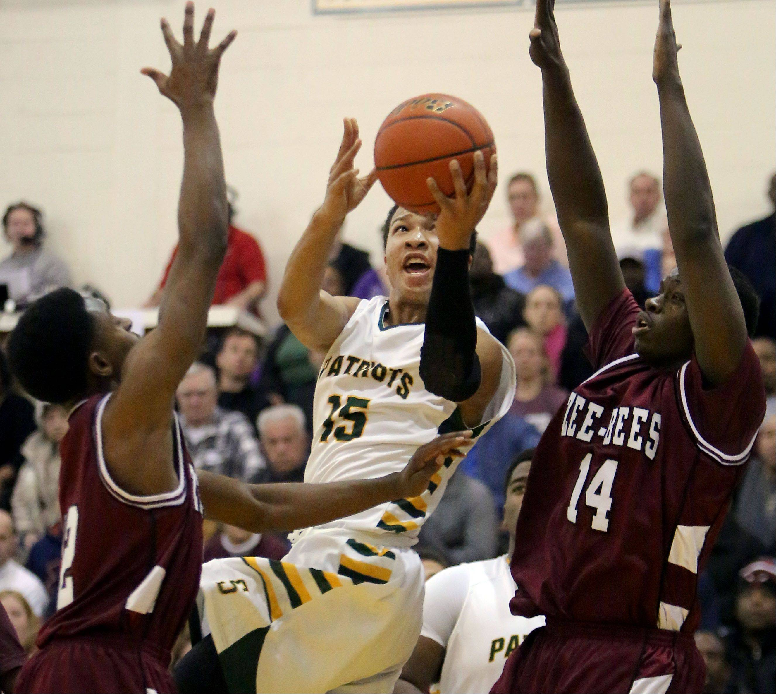 Stevenson's Jalen Brunson, middle, splits between Zion Benton's Mubarak Bakr, left, and Milik Yarbrough.