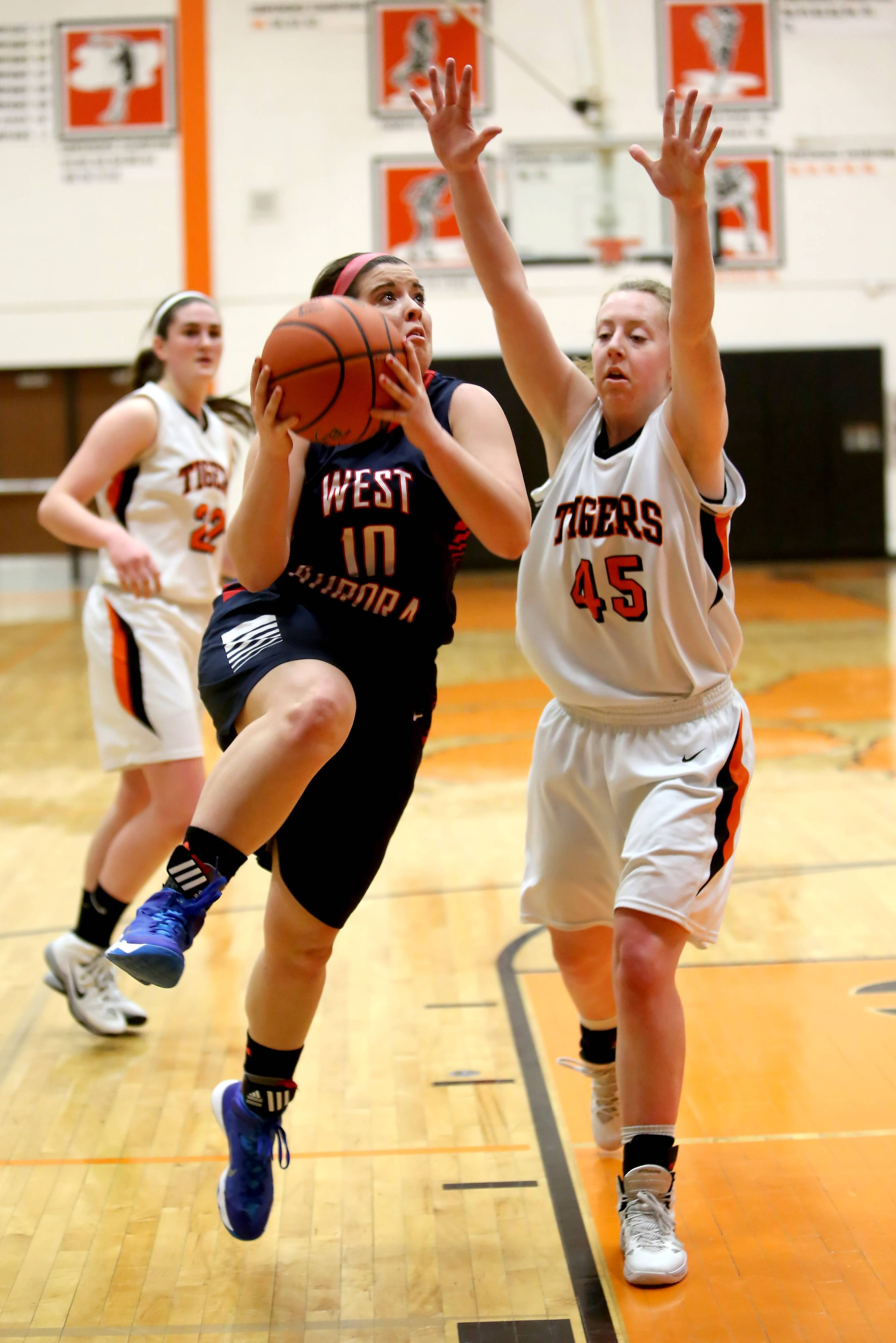 West Aurora's Taylor Jacobsen moves past Meghan Waldron of Wheaton Warrenville South, right, to attempt a basket in girls basketball action on Monday in Wheaton.