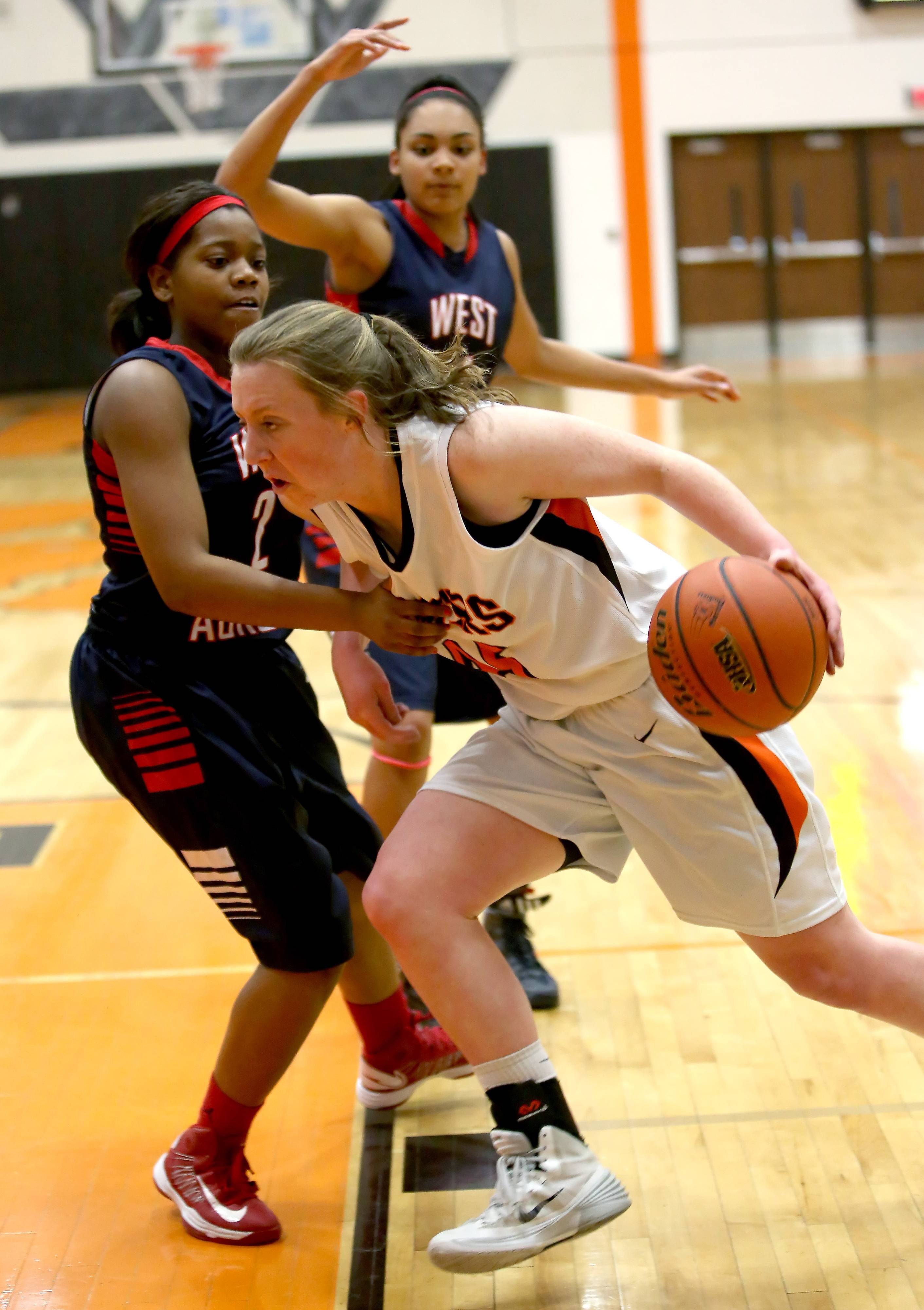 Wheaton Warrenville South's Meghan Waldron drives past Ashley Williams, left, of West Aurora in girls basketball action on Monday in Wheaton.