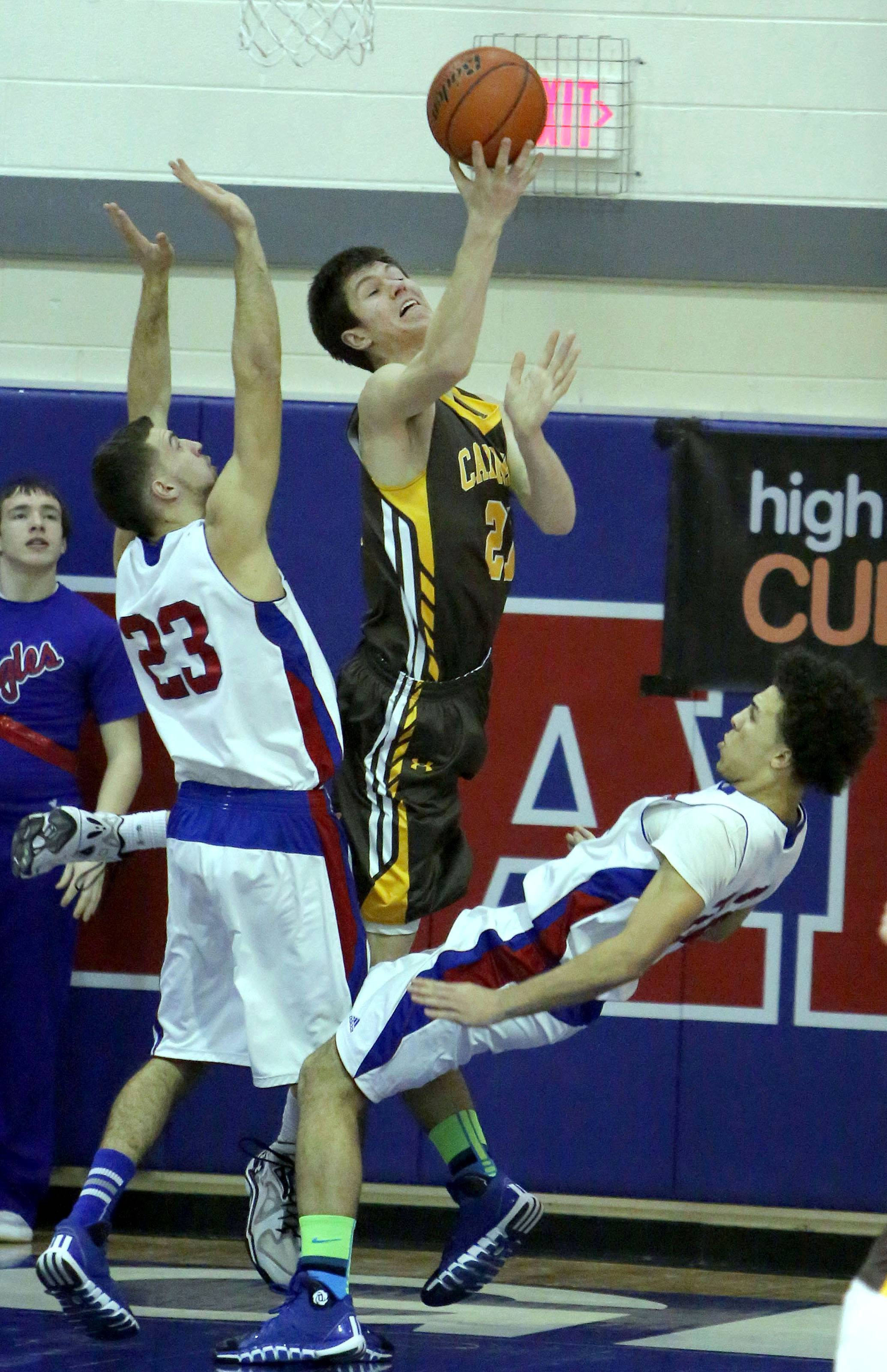 Carmel's Jack George, middle, drives on Lakes' Mike Tomasiewicz, left, and Tramone Hudson on Monday night at Lakes.
