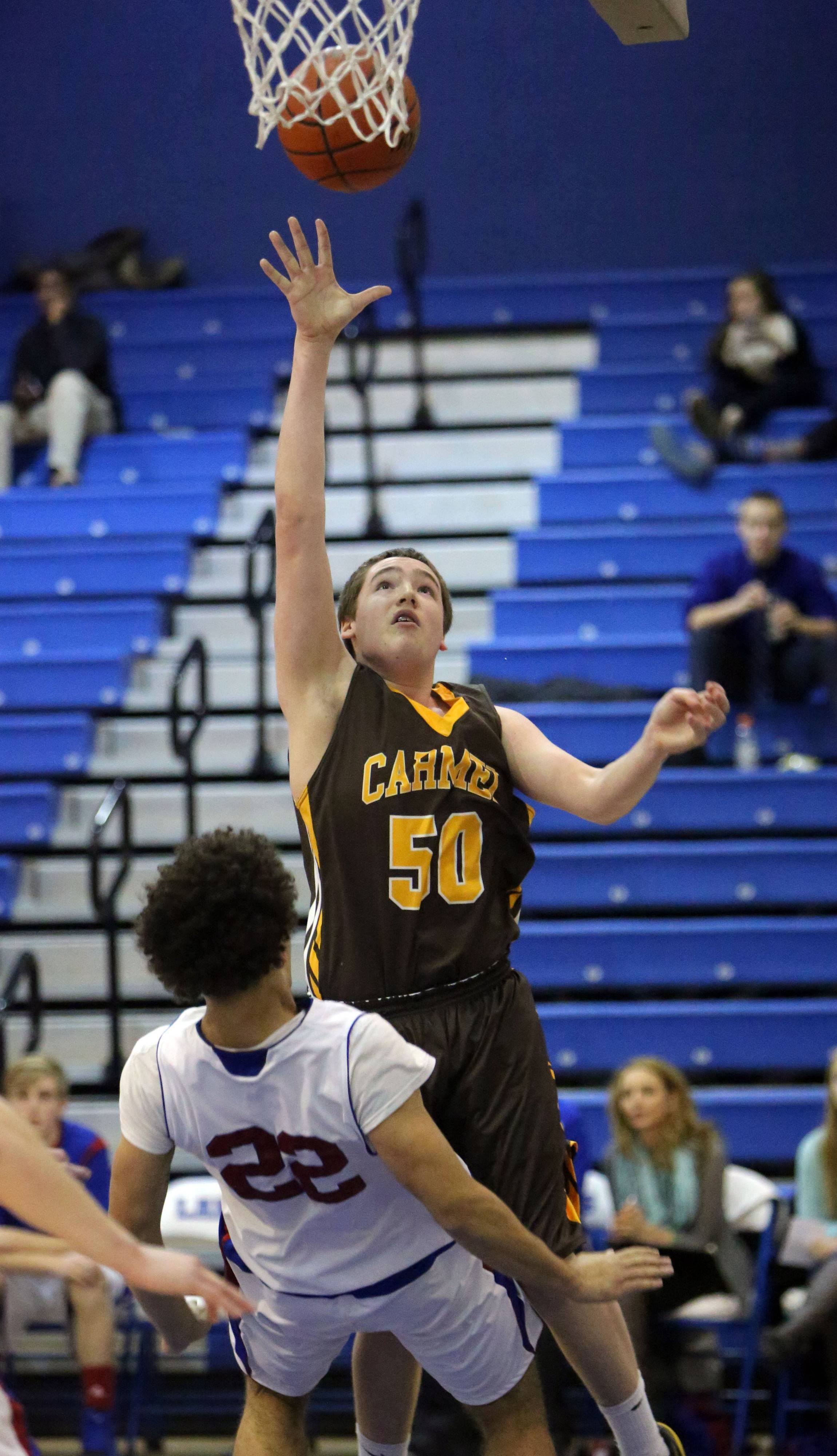 Carmel's Lee Bowen, right, is called for a charge as he drives on Lakes' Tramone Hudson on Monday night at Lakes.