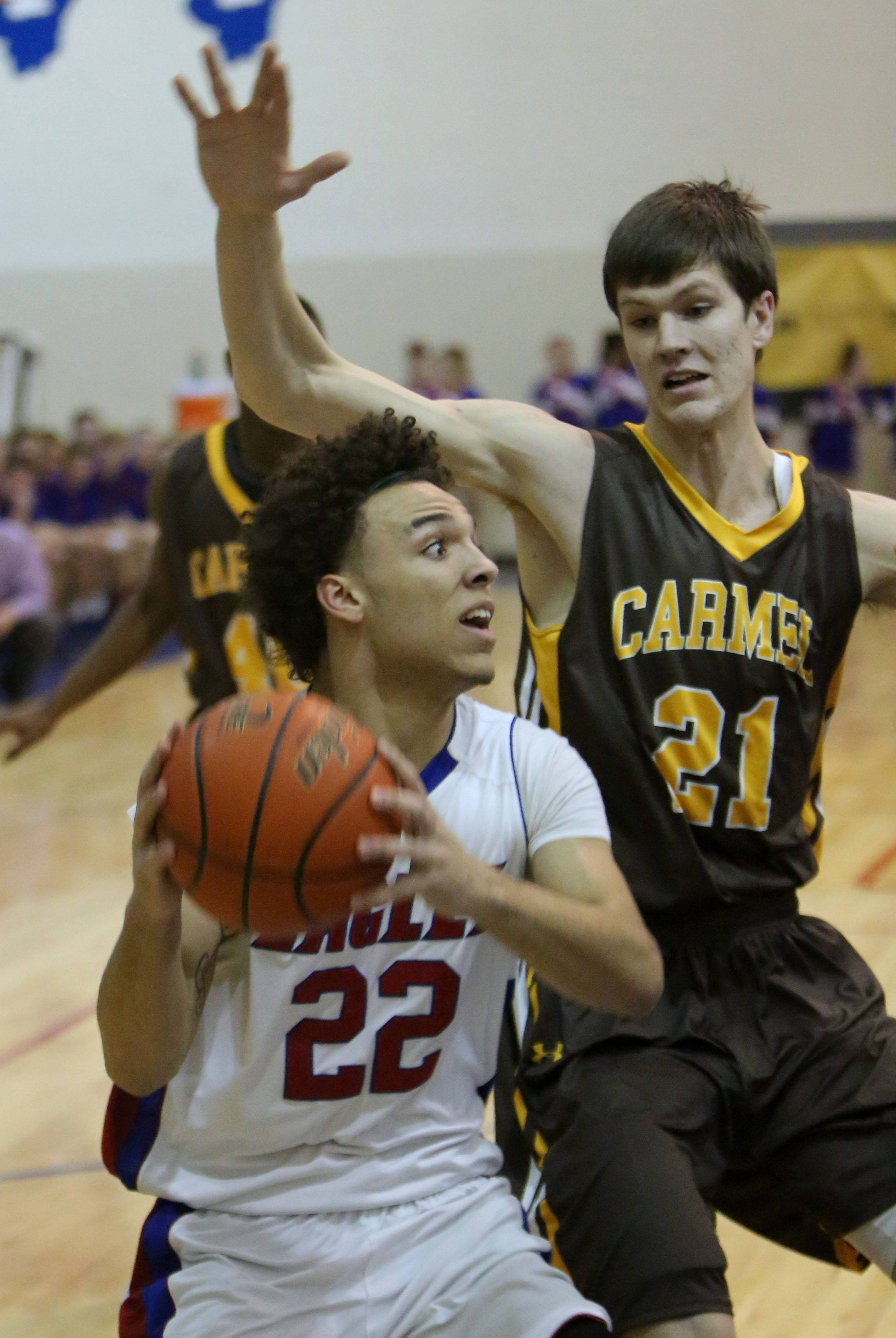 Lakes' Carmel's Tramone Hudson, left, drives to the hoop on Carmel's Jack George.