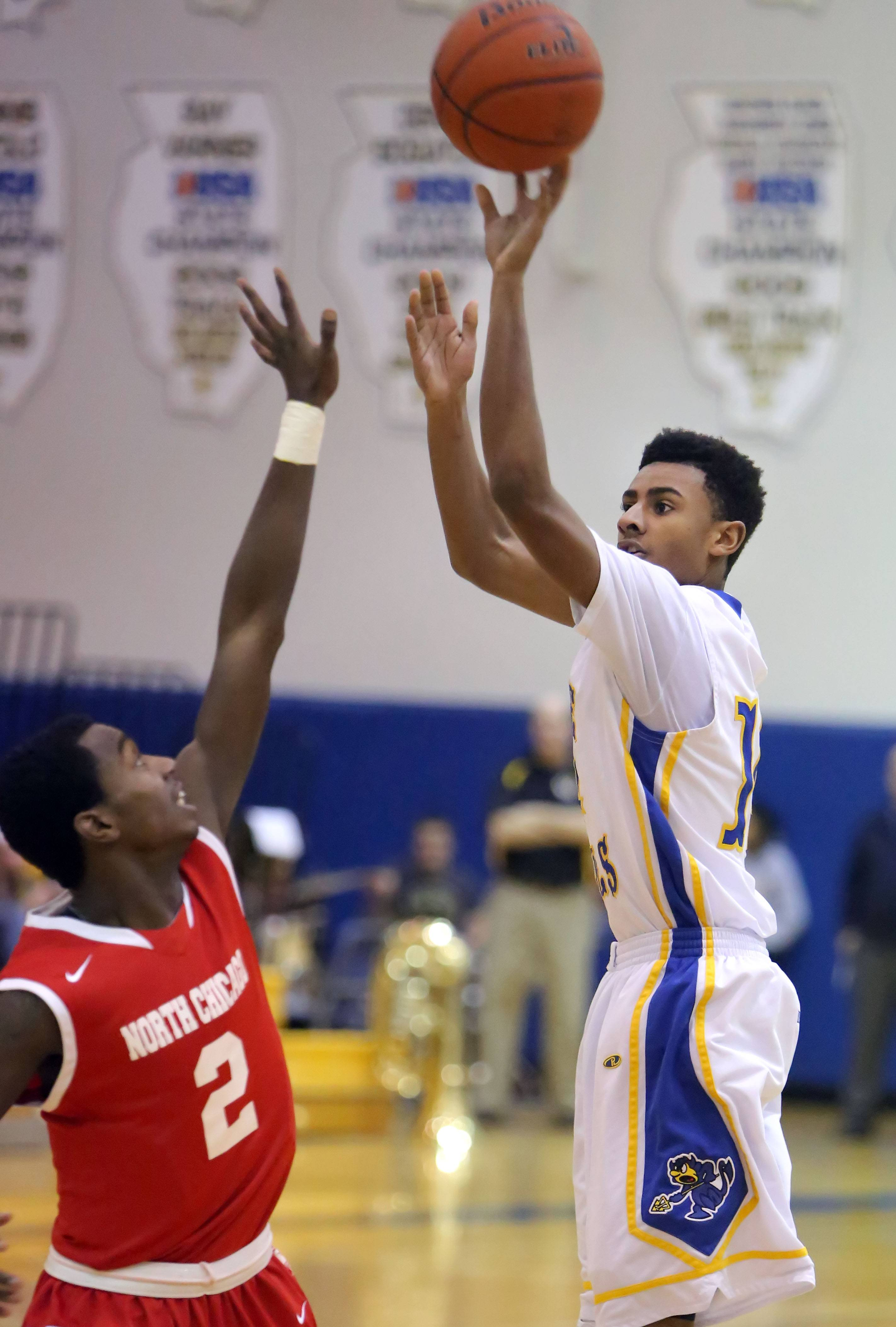 Warren's Adrian Deere, right, shoots over North Chicago's JaVairius Amos-Mays on Tuesday night at Warren.