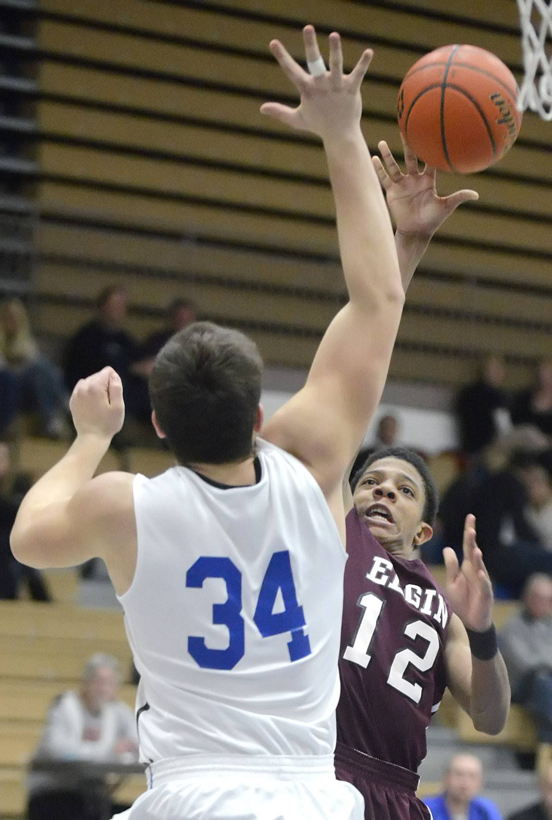 Elgin's Donte Harper shoots around and over a block by St. Charles North's Garrett Johnson in the third quarter on Tuesday, February 11.