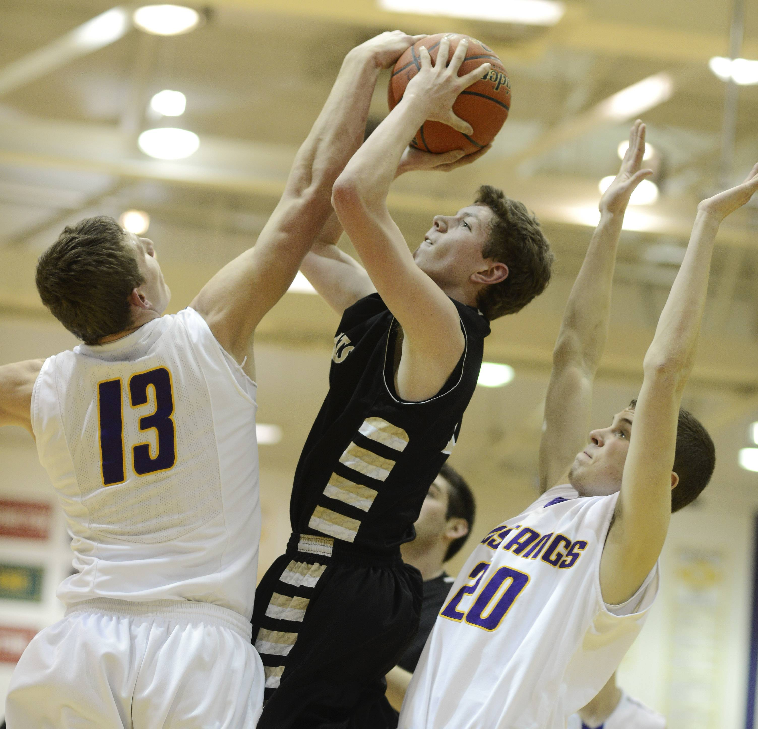 Graylake North's Lucas Buckels attempts a shot against Rolling Meadows defenders Matt Dolan, left, and Charlie Metzger during Tuesday's game at Rolling Meadows.