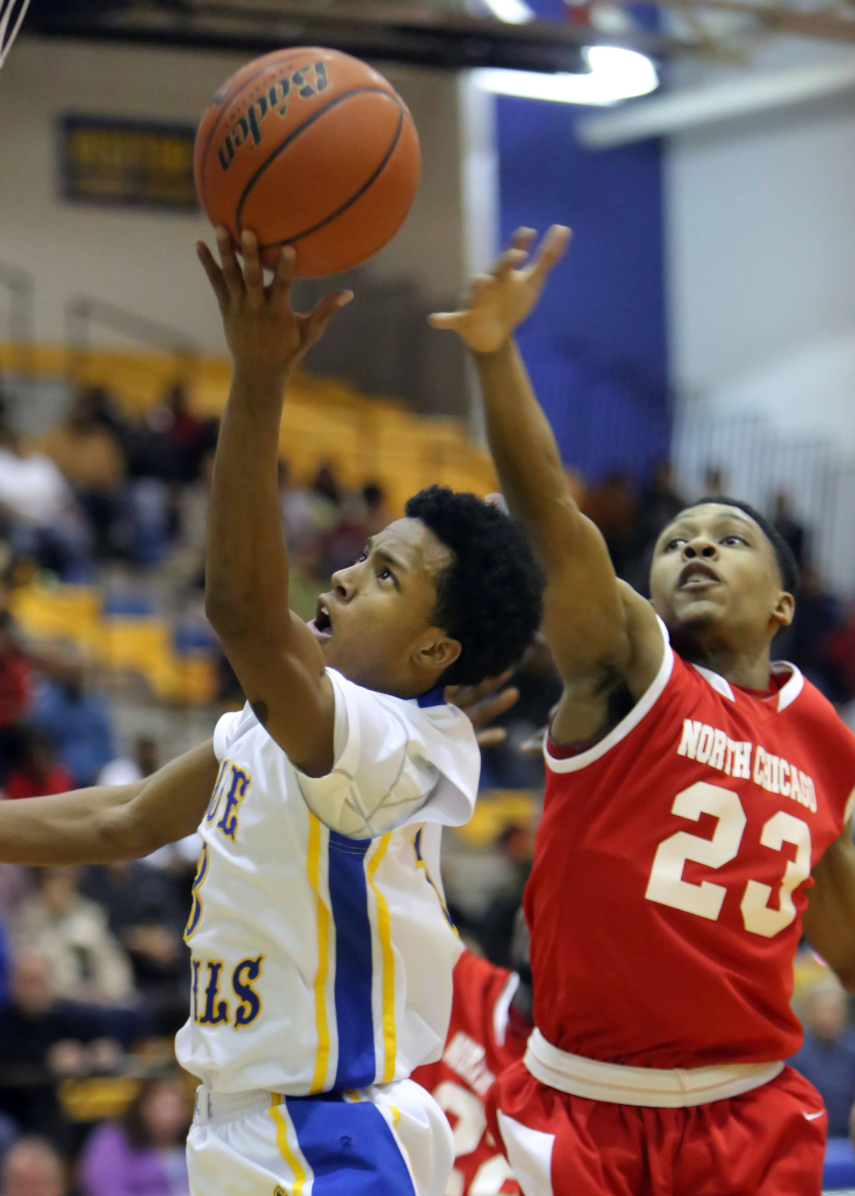 Warren's Eric Gillespie, left, drives past North Chicago's Jamero Shelton.