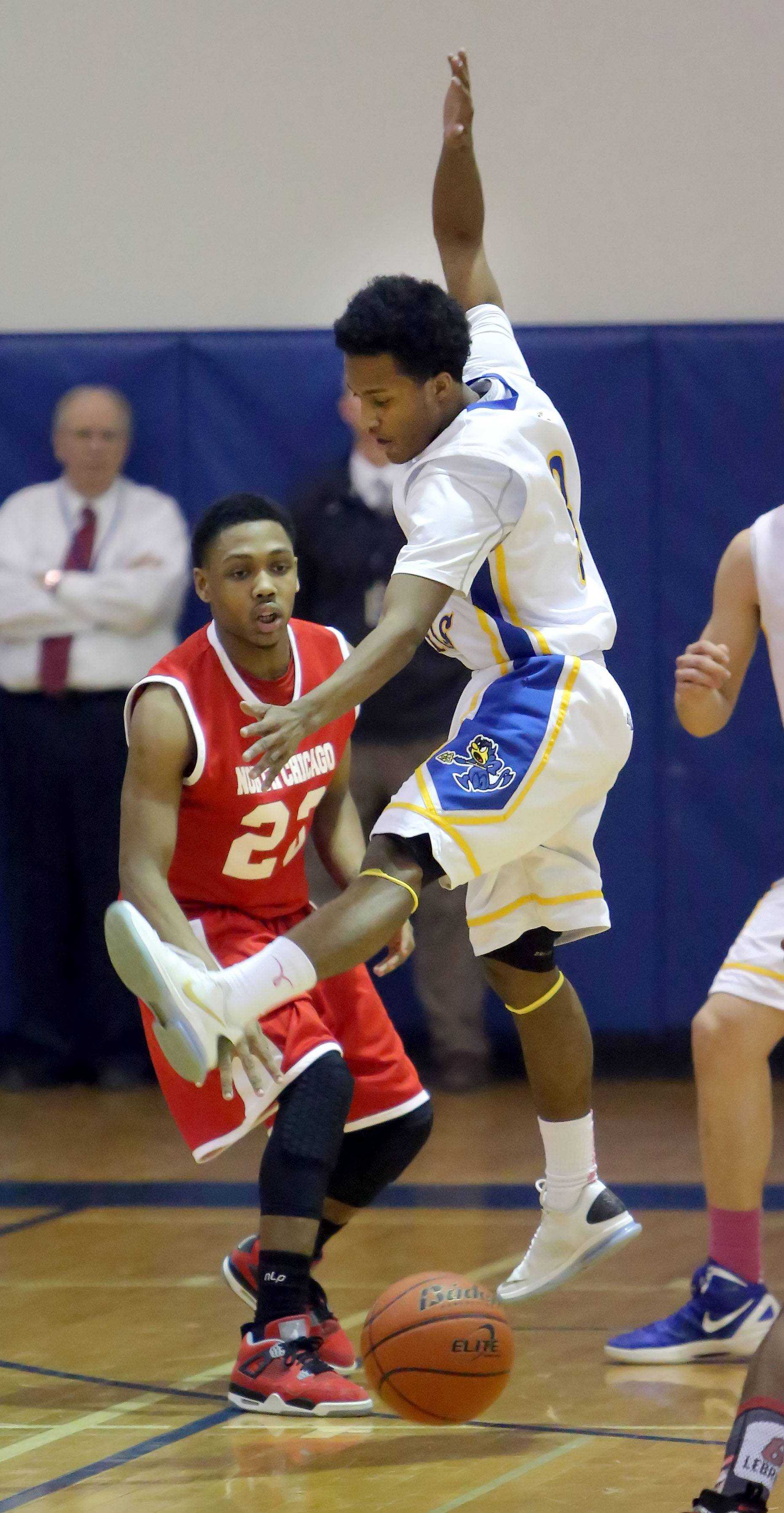 Warren's Eric Gillespie, right, defends against North Chicago's Jamero Shelton.
