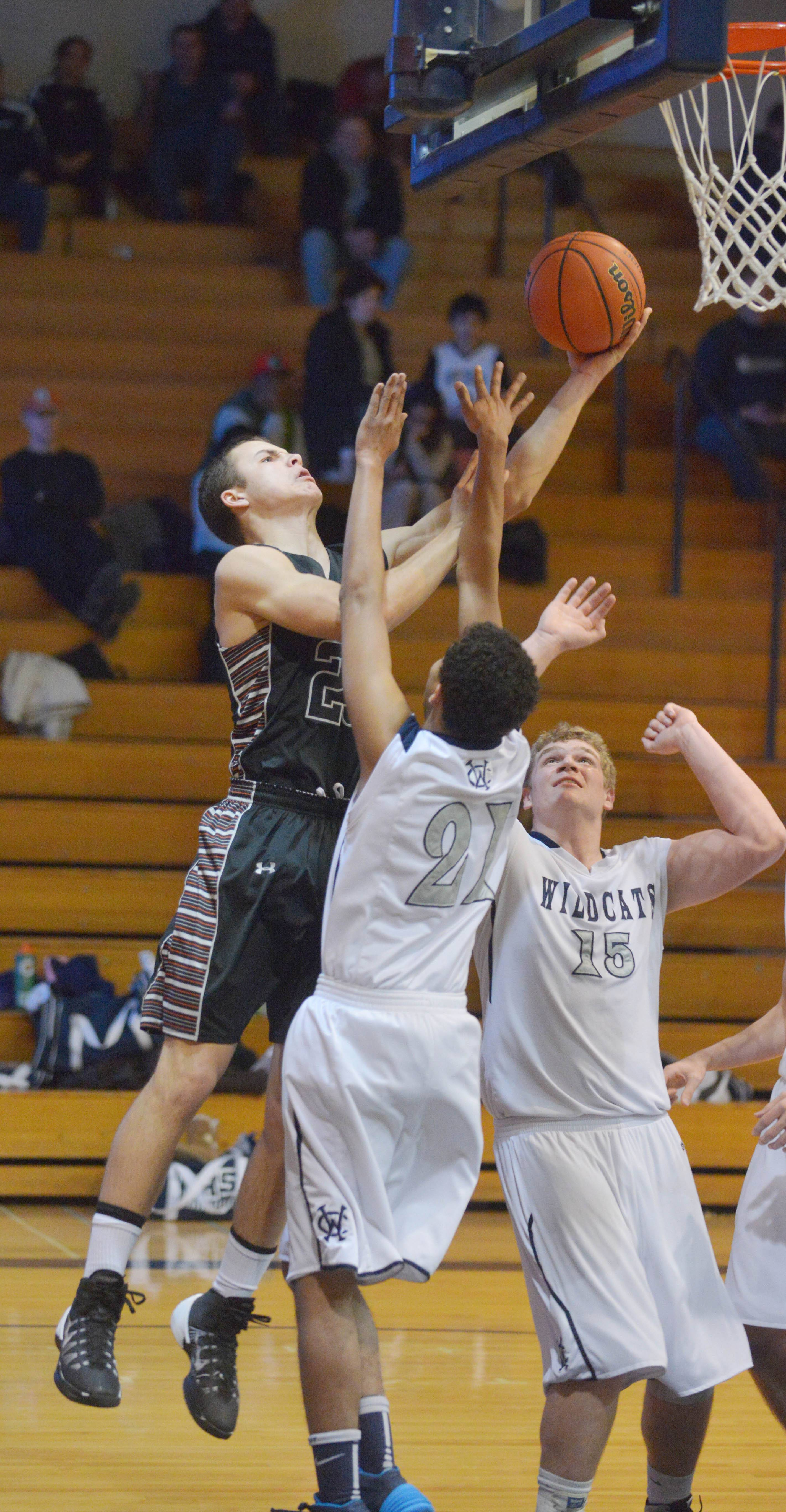 Kaneland's Tyler Carlson takes a shot over Michael Bibbs and Ethan Doell of West Chicago.