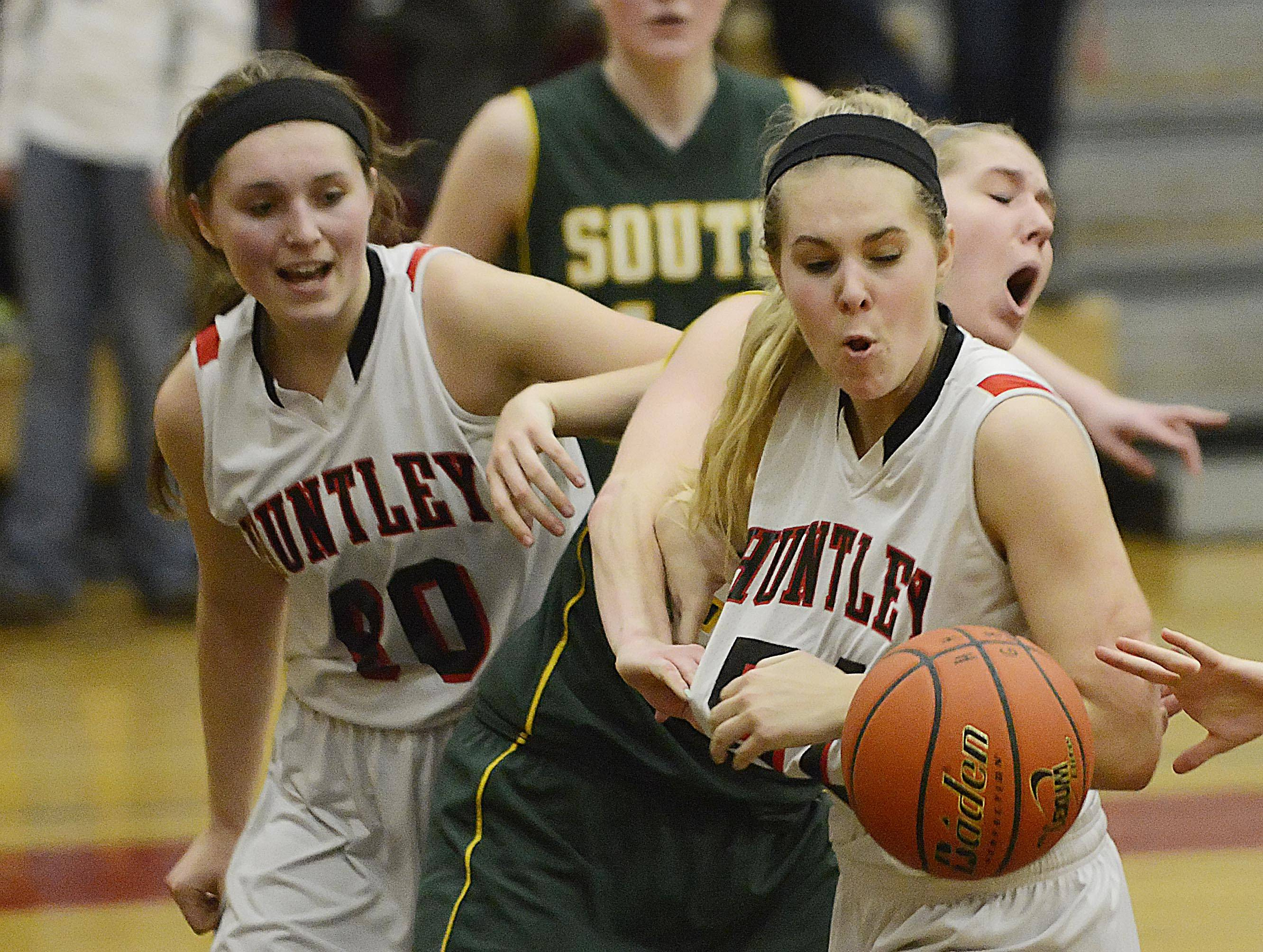 Huntley sister Sam, left, and Ali Andrews, right, battle for the ball against Crystal Lake South's Sara Mickow .
