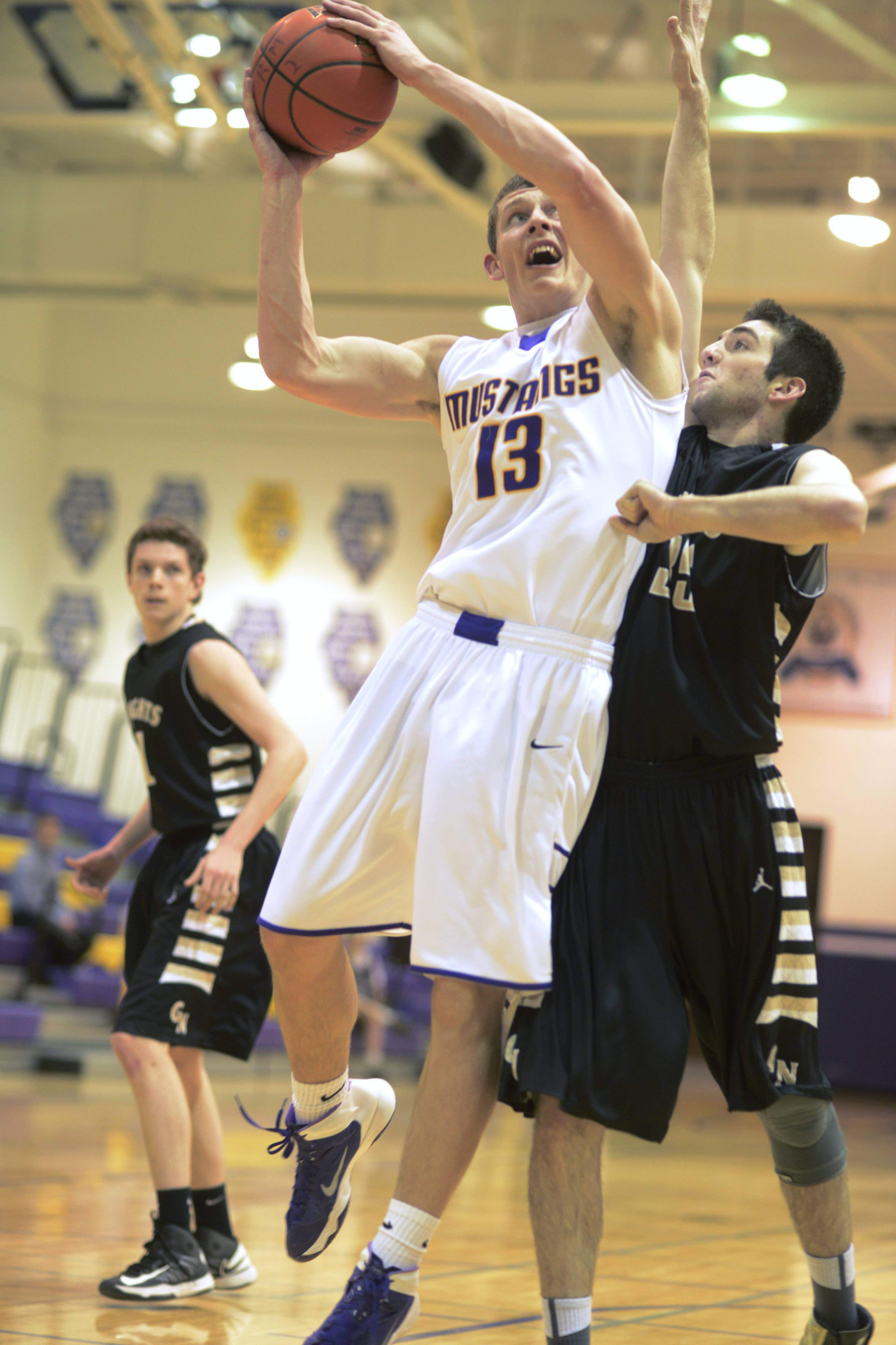 Rolling Meadows' Matt Dolan, left, drives to the basket against Grayslake North defender Drew Piggott.
