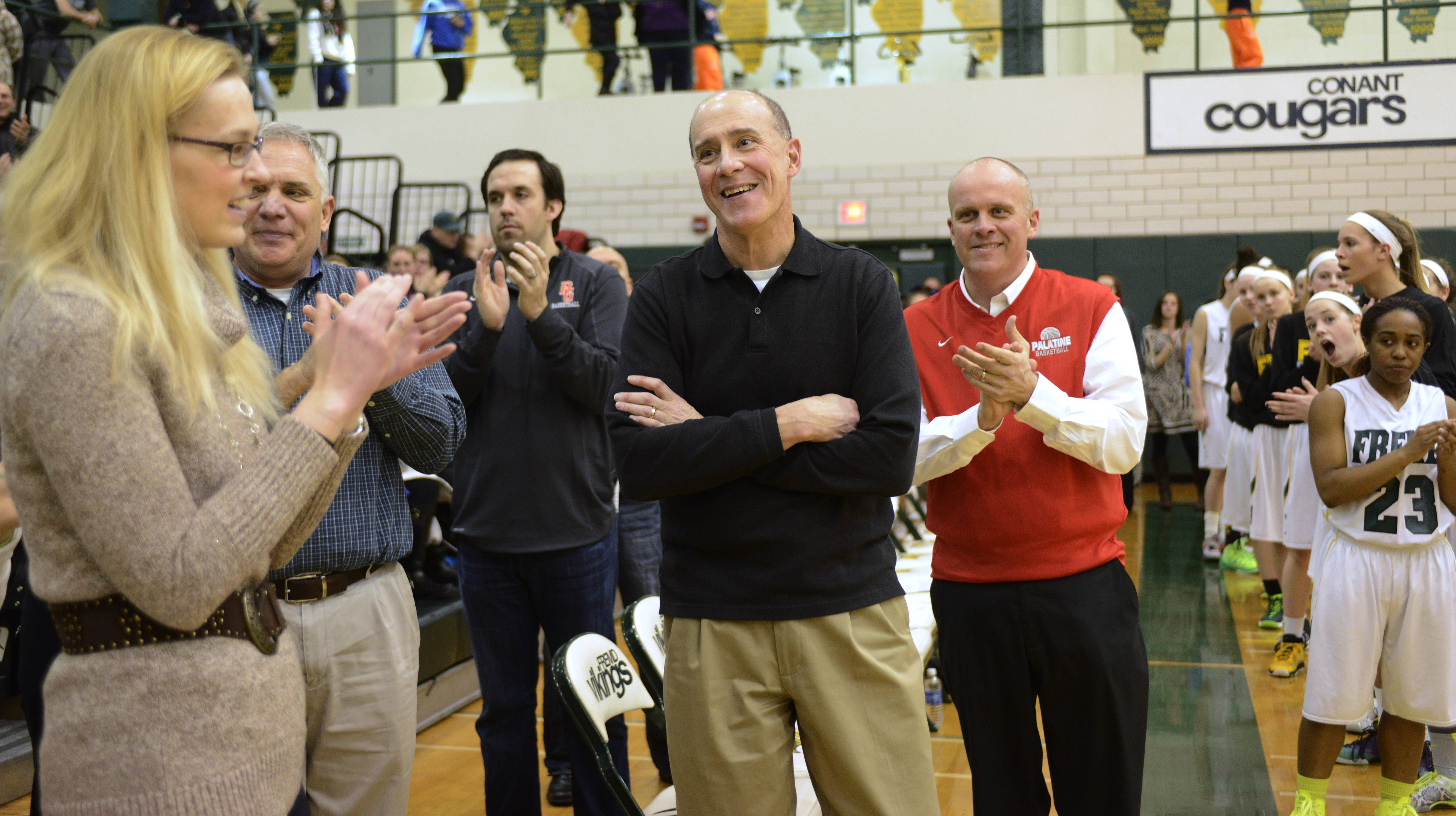 Retiring Conant coach Dan Travers, middle, is honored by fellow coaches prior to Wednesday's Mid Suburban League championship game in Palatine.