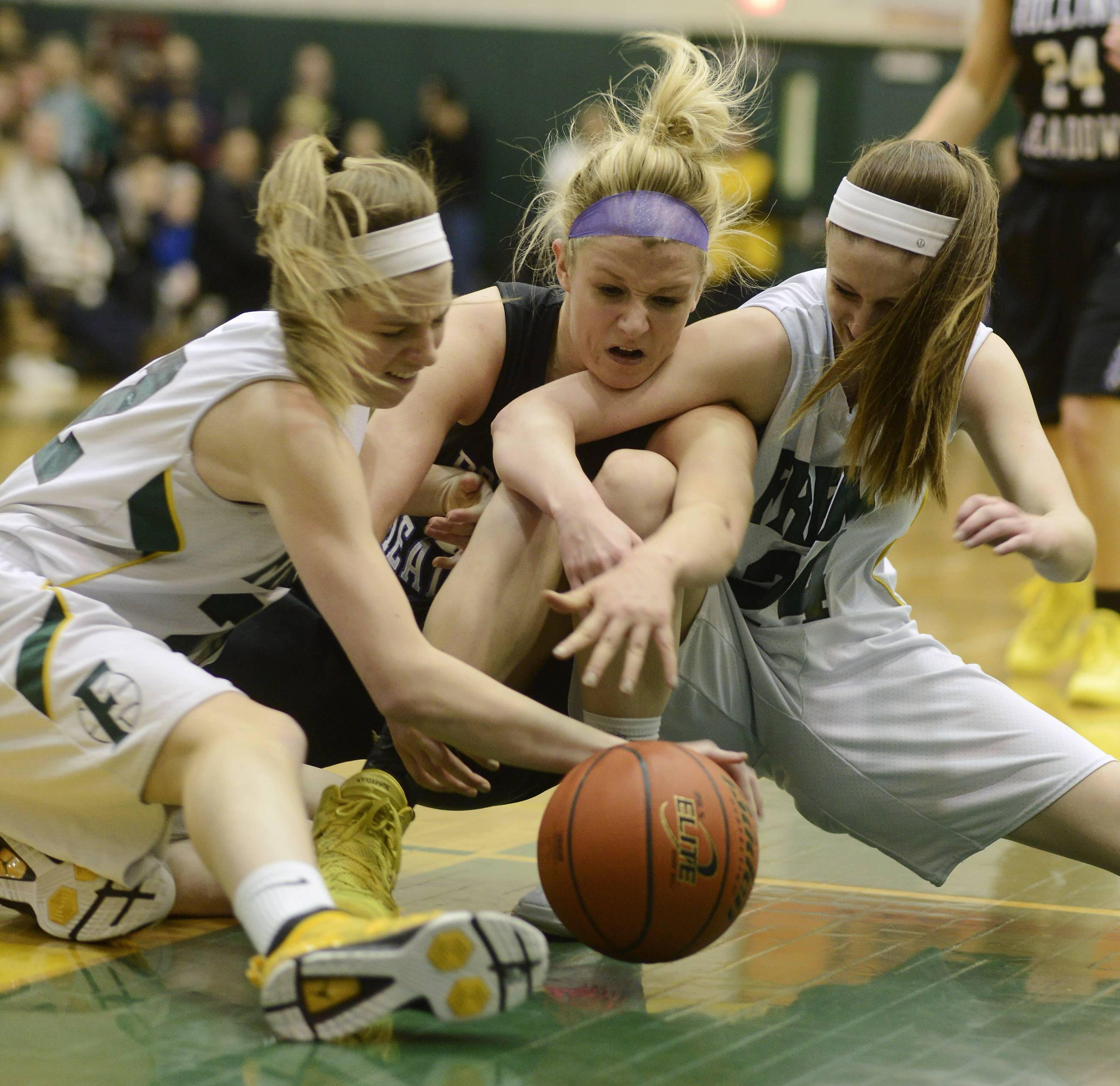 Rolling Meadows' Jenny Vliet gets between Fremd's Erin Lenahan, left, and Hannah LaBarge, right, in an attempt to control a loose ball during Wednesday's Mid-Suburban League championship game in Palatine.
