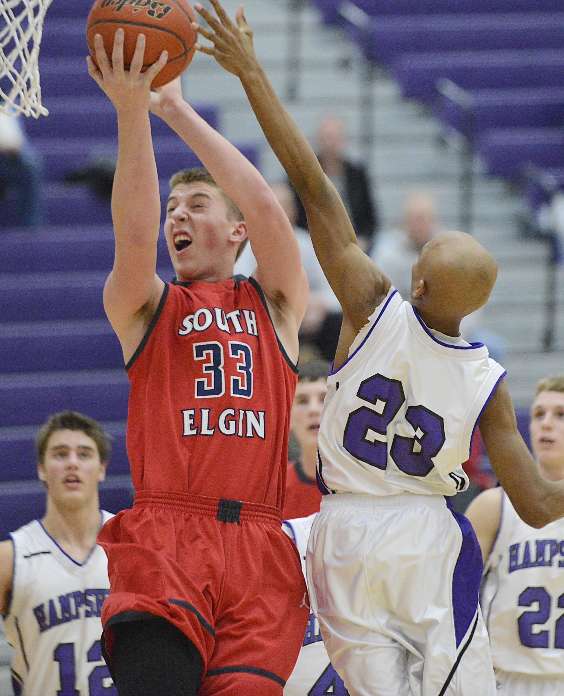 South Elgin's Jake Amrhein is fouled by Hampshire's Nico Bennett Wednesday in Hampshire.
