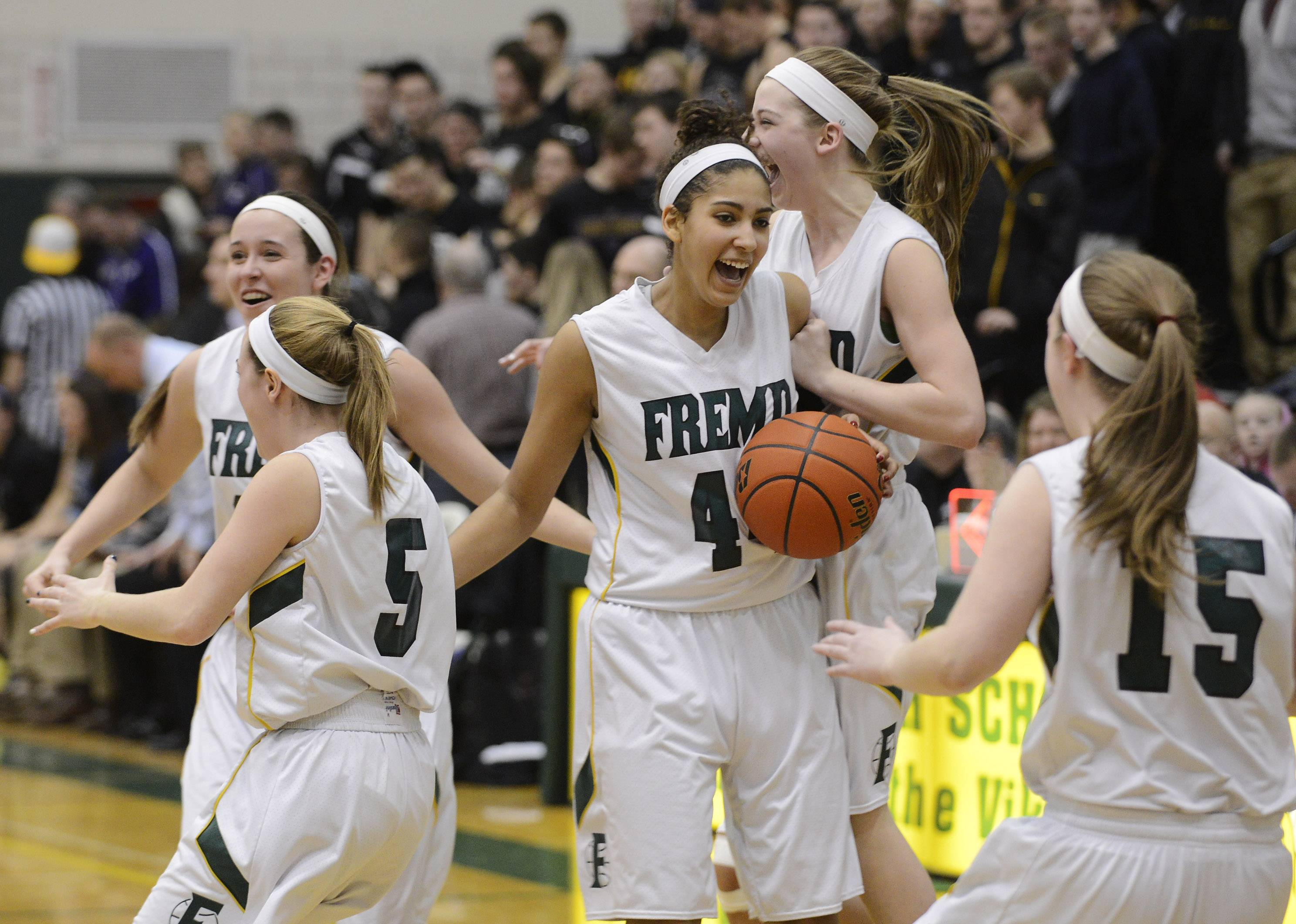 Fremd players, including Bryana Hopkins, with ball, celebrate their victory over Rolling Meadows.