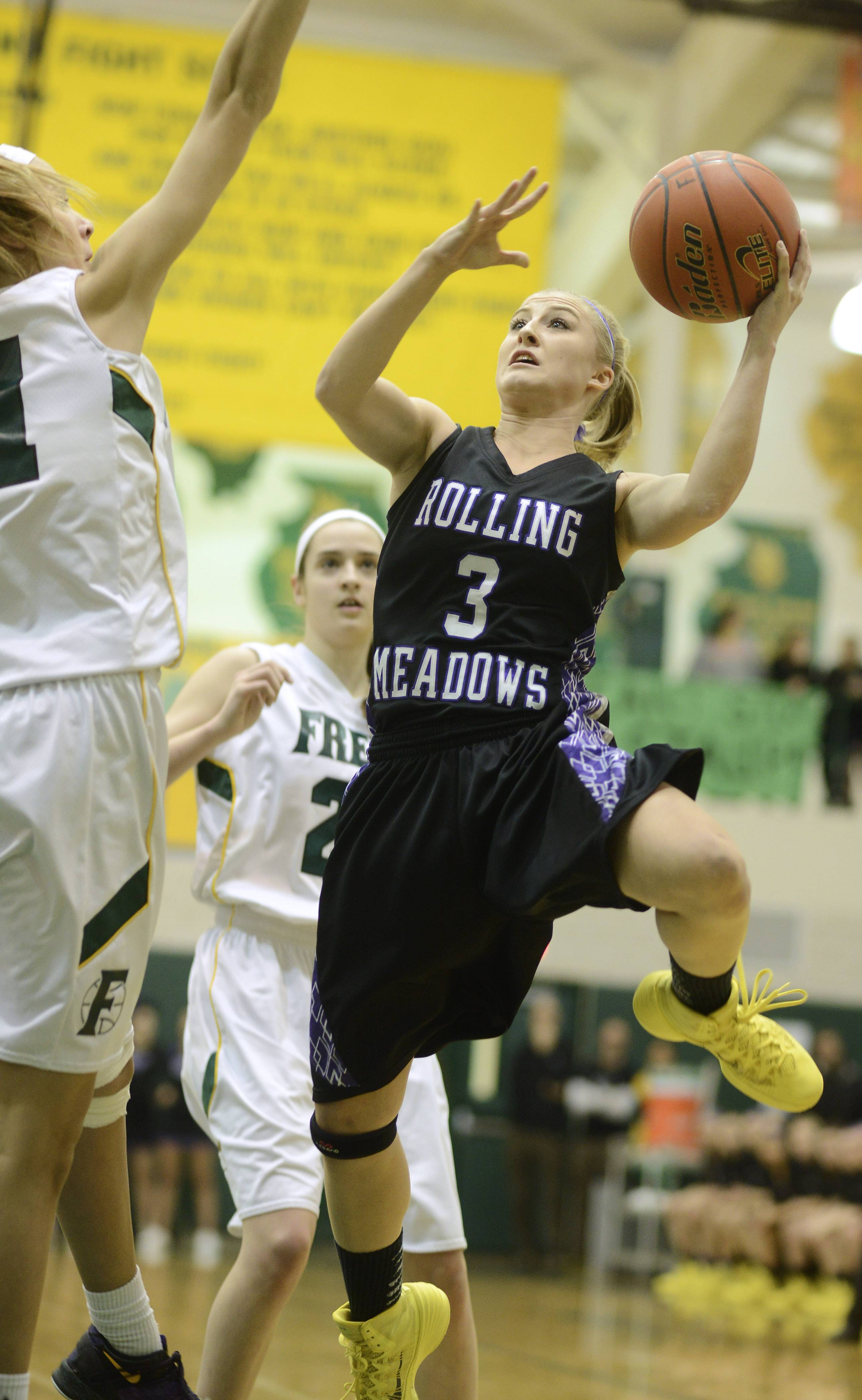 Rolling Meadows' Jackie Kemph drives to the basket against the Fremd defense, including Grace Tworek, left.