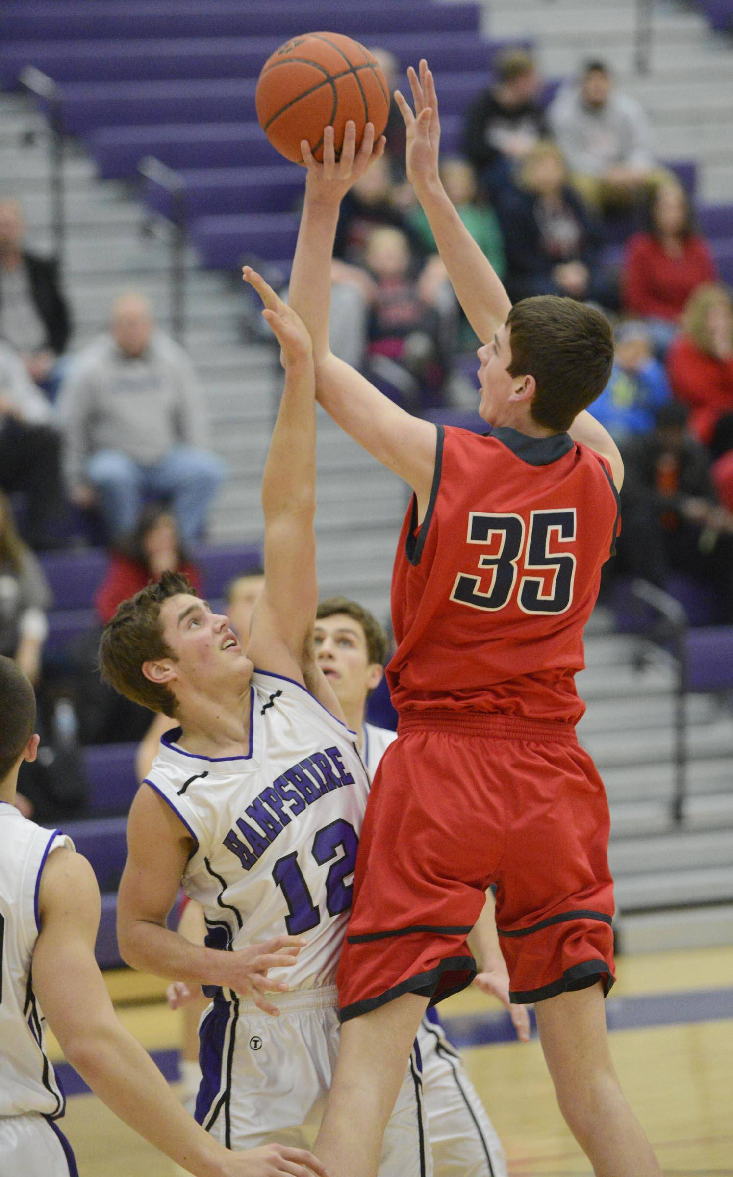 South Elgin's Tyler Hankins turns and shoots over Hampshire's Matthew Bridges .