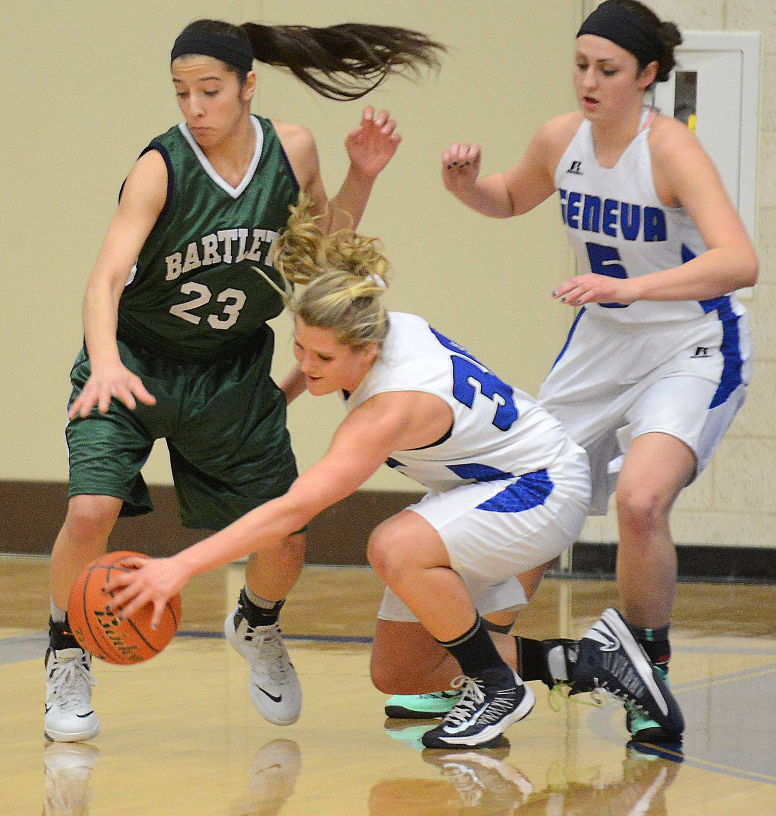 Geneva's Janie McCloughan dives for a loose ball in front of Bartlett's Ally Giampapa .