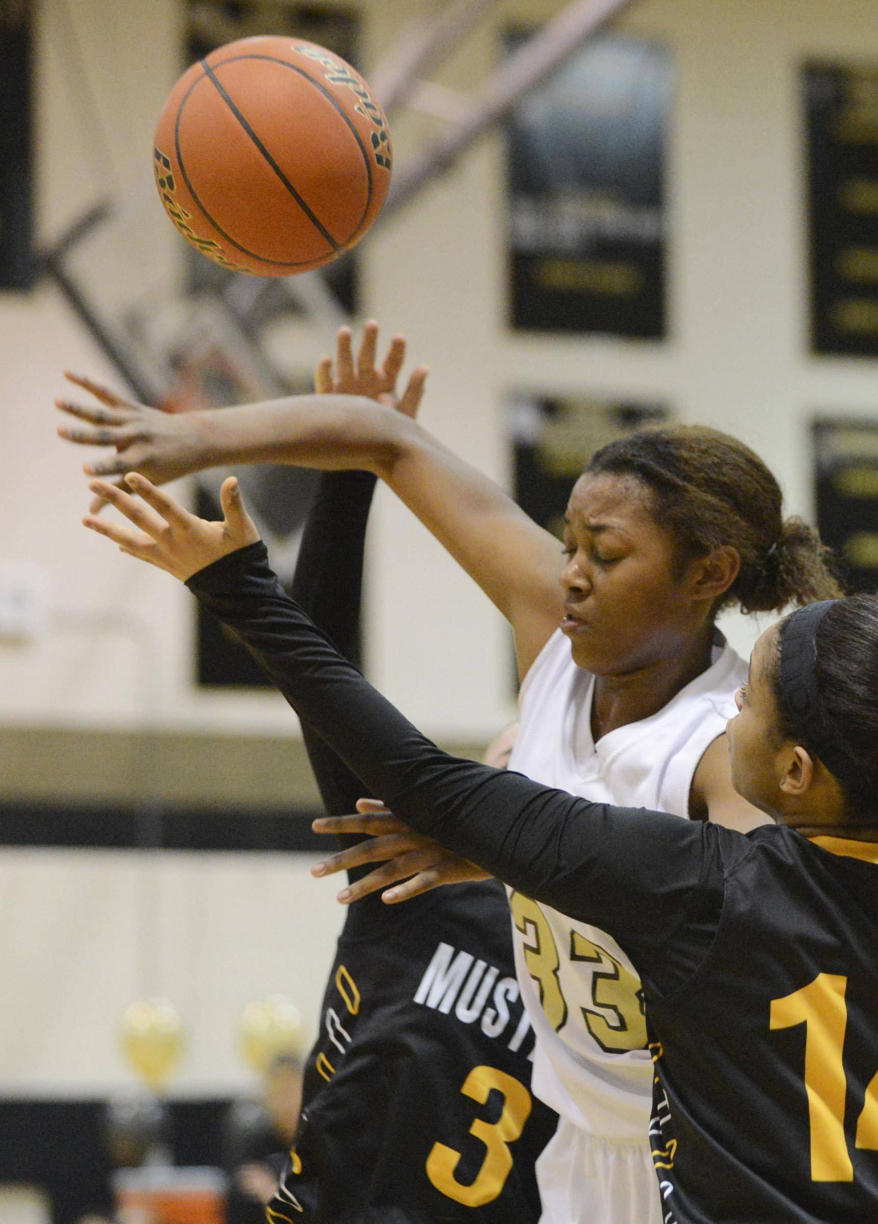 Streamwood's Jenejha Williams loses control of the ball under pressure from Metea Valley's Lisa Logan and Kellee Clay, foreground.