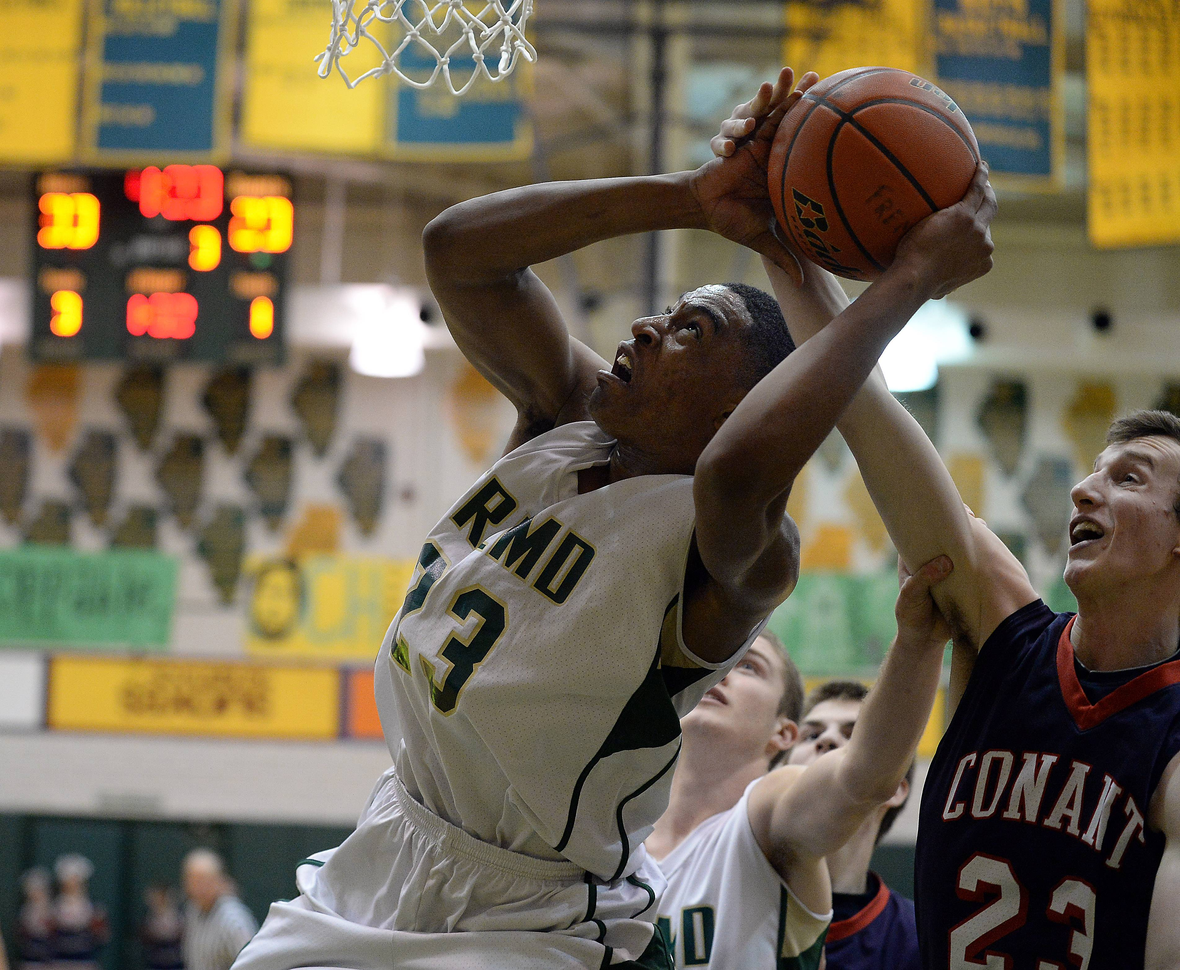 Fremd's Xavier Williams (23) eyes the basket but is fouled by Conant's Drew Lydon (23) in MSL West play at Fremd on Friday.