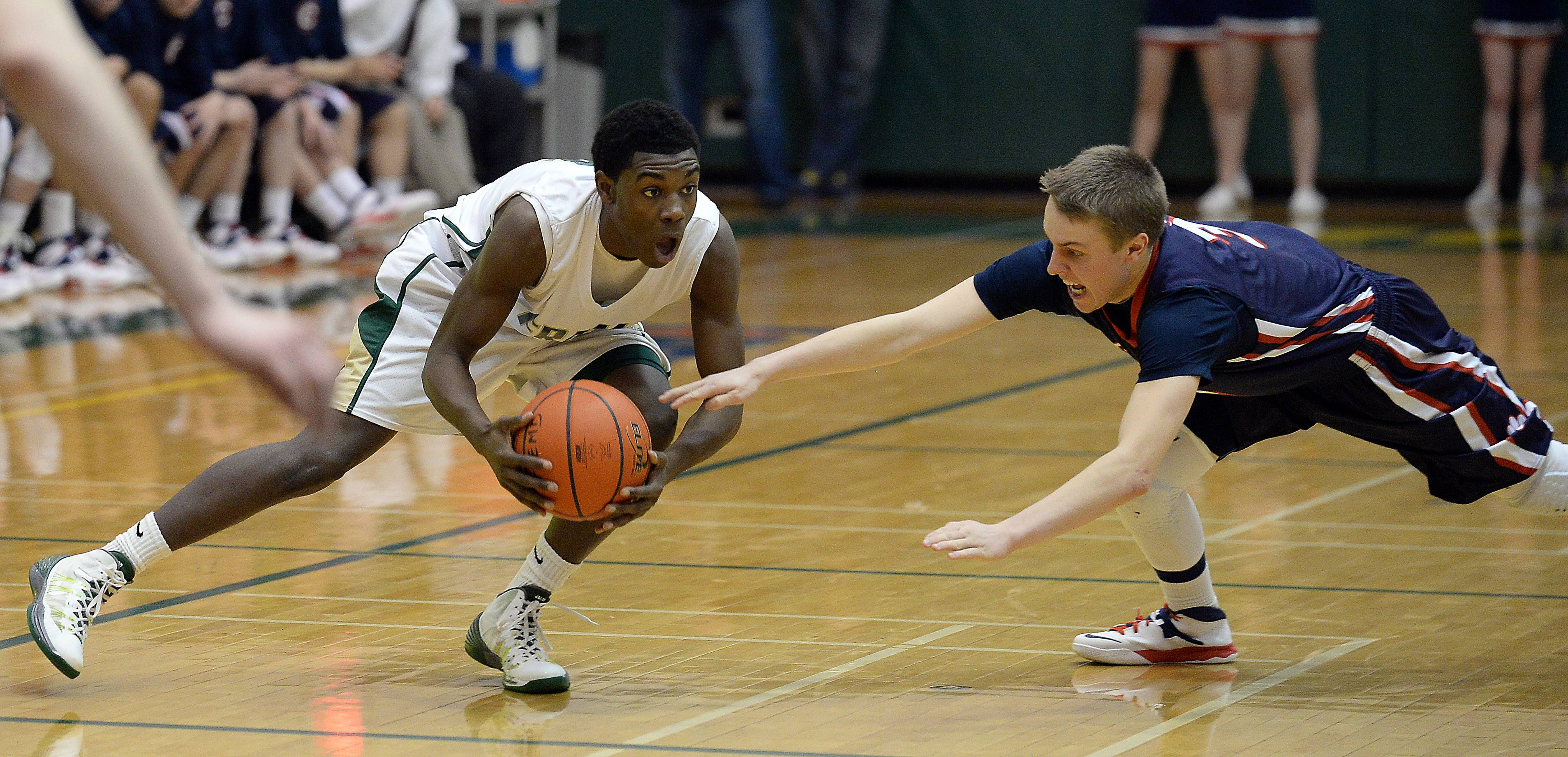 Fremd's Jalon Roundy tries to maintain control of the ball as Conant's Kevin Copher comes in and knocks it away.
