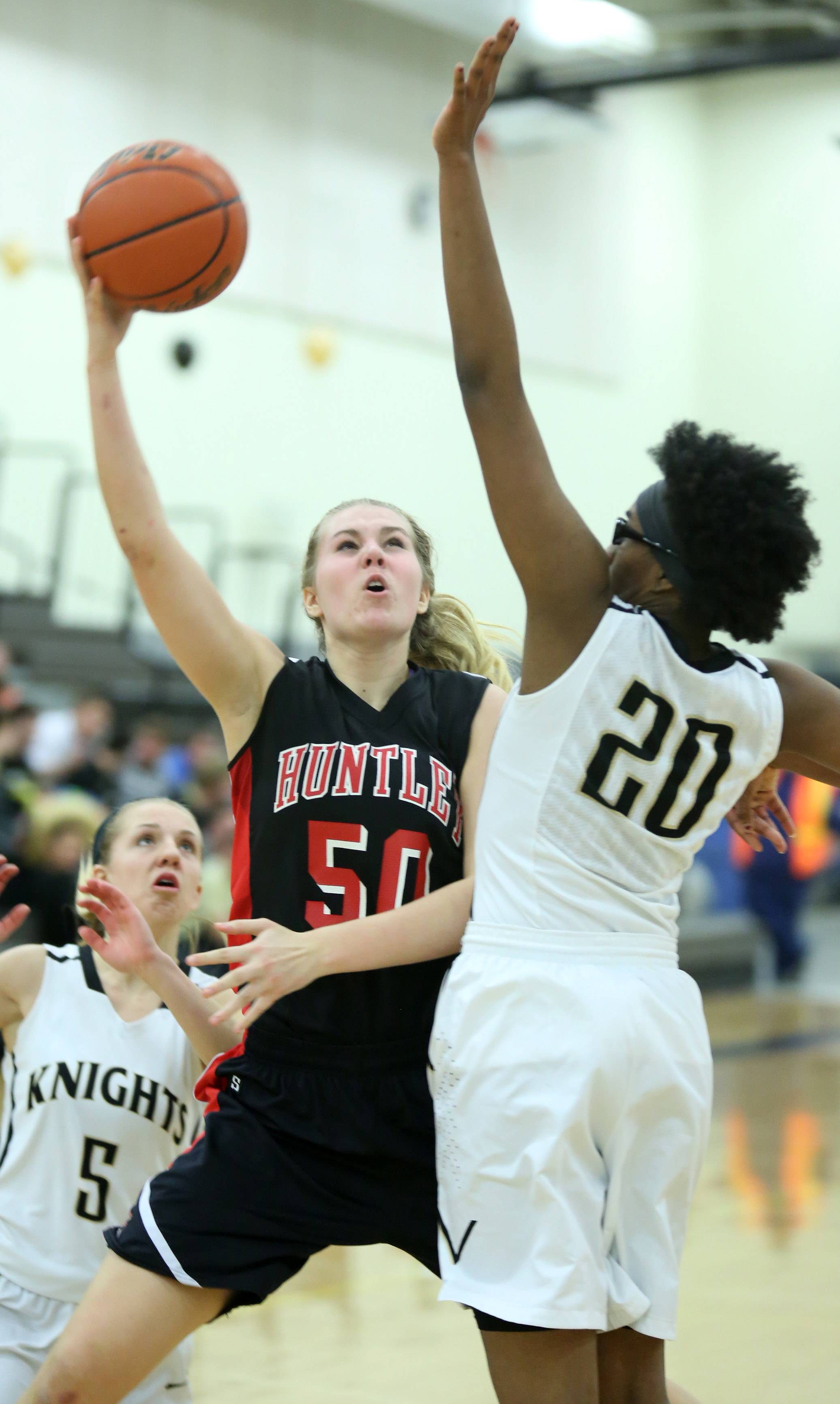 Huntley forward Ali Andrews shoots around Grayslake North defender Brittany Thiebeaux.