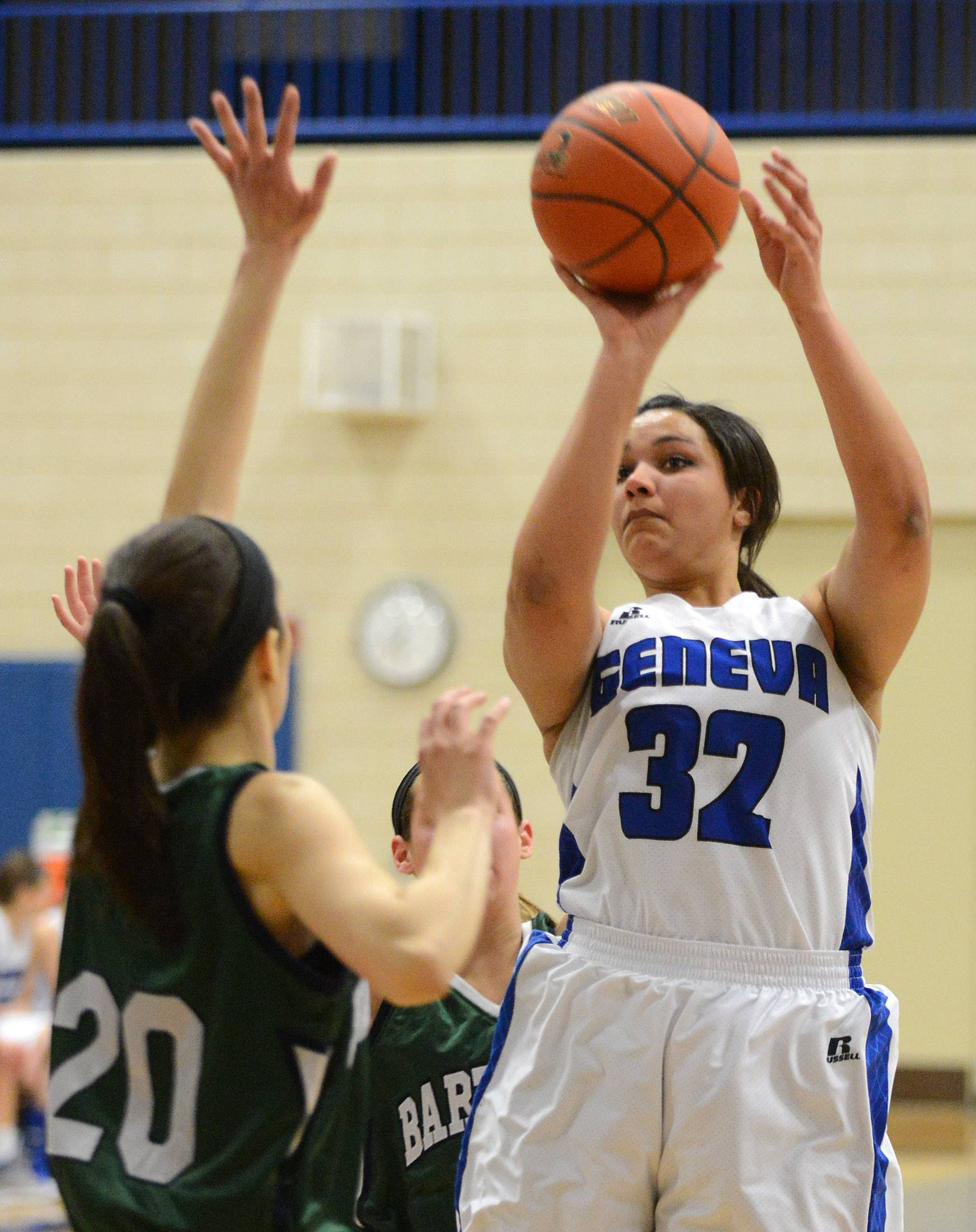 Rick West/rwest@dailyherald.com  Geneva's Sidney Santos (32) shoots and scores over Bartlett's Elizabeth Arco (20) during Thursday's game in Geneva.