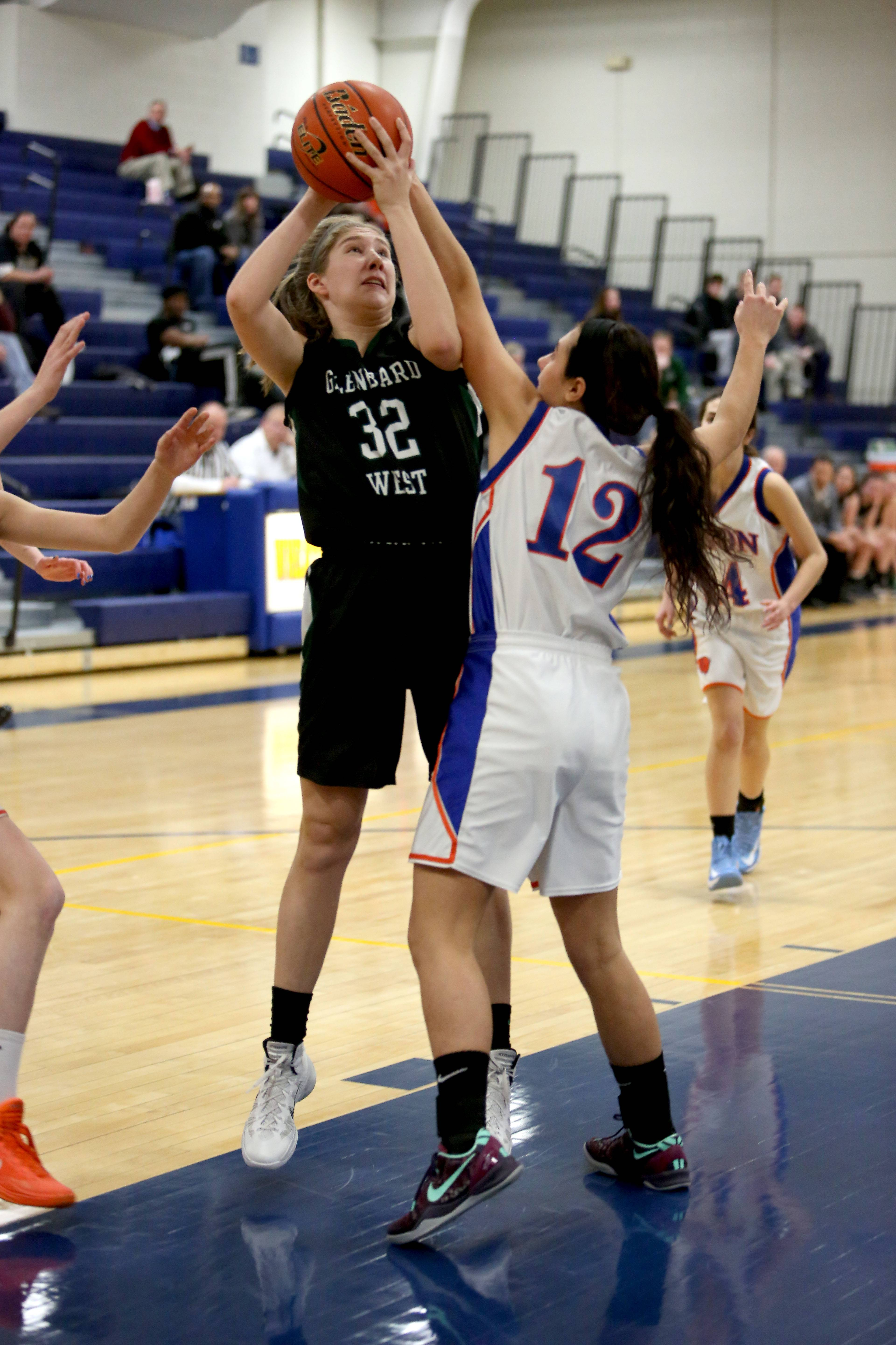 Ellen Daniels of Glenbard West, left, looks to shoot the ball as Rachael Leschewski of Fenton, right, defends in regional quarterfinal girls basketball at Wheaton North on Monday.