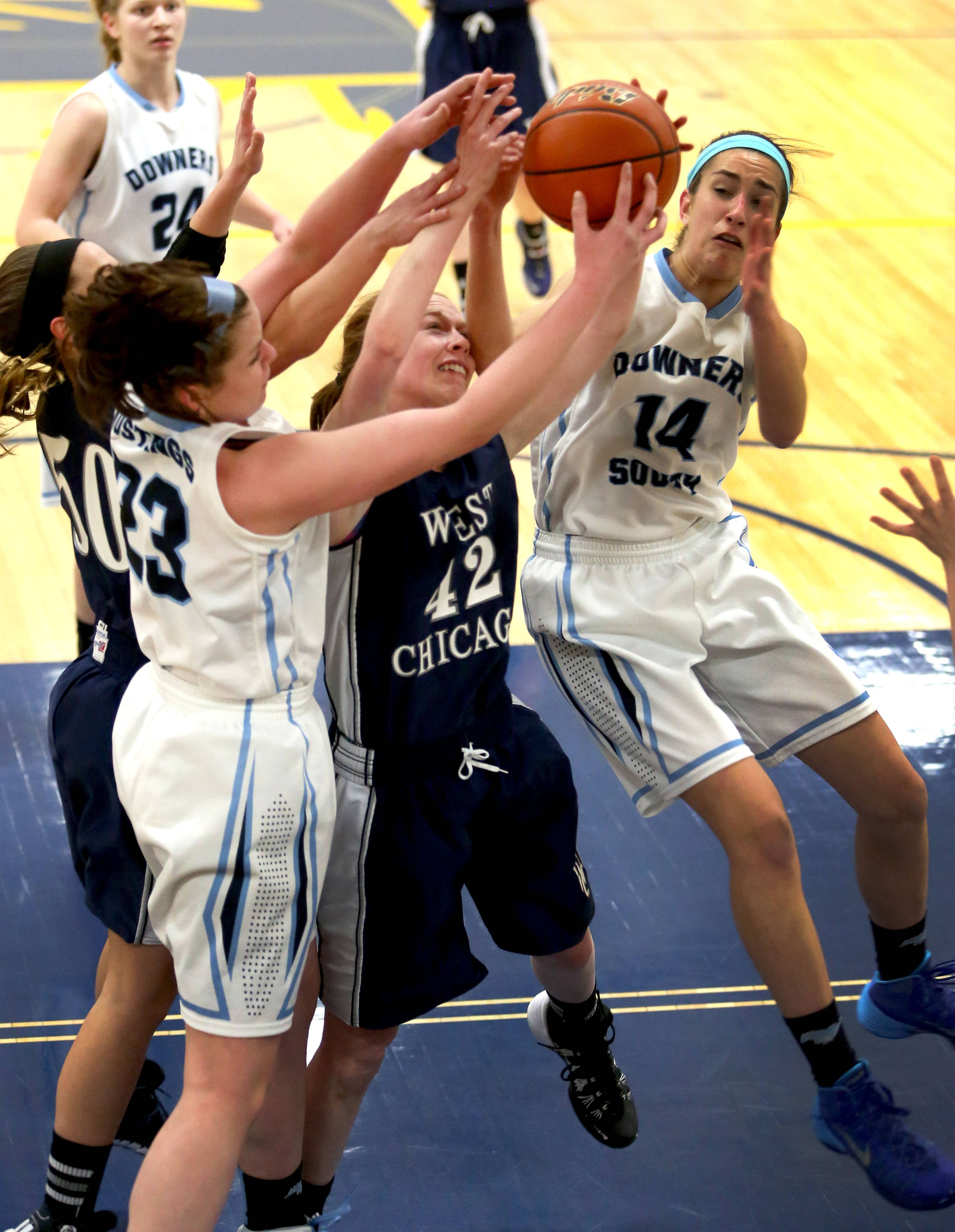West Chicago's Madeline Earls, center, gets tangled with Noicole Landrosh, left and Claire Hardy, right, of Downers Grove South on a rebound.