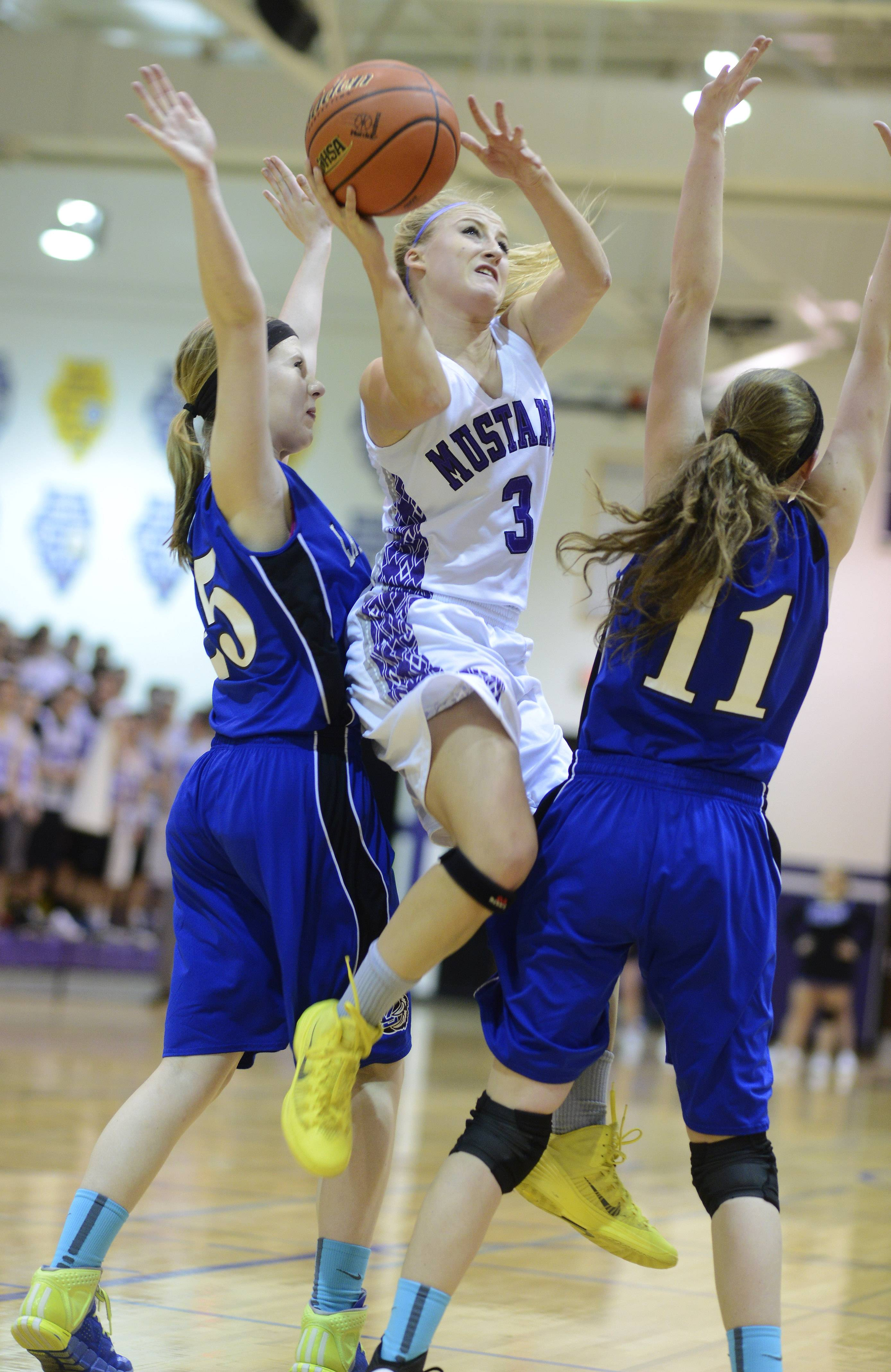 Rolling Meadows' Jackie Kemph, middle, steps between Lake Zurich's Abby Pirron, left, and Rachel Dawson for a layup during Tuesday's regional semifinal at Rolling Meadows.
