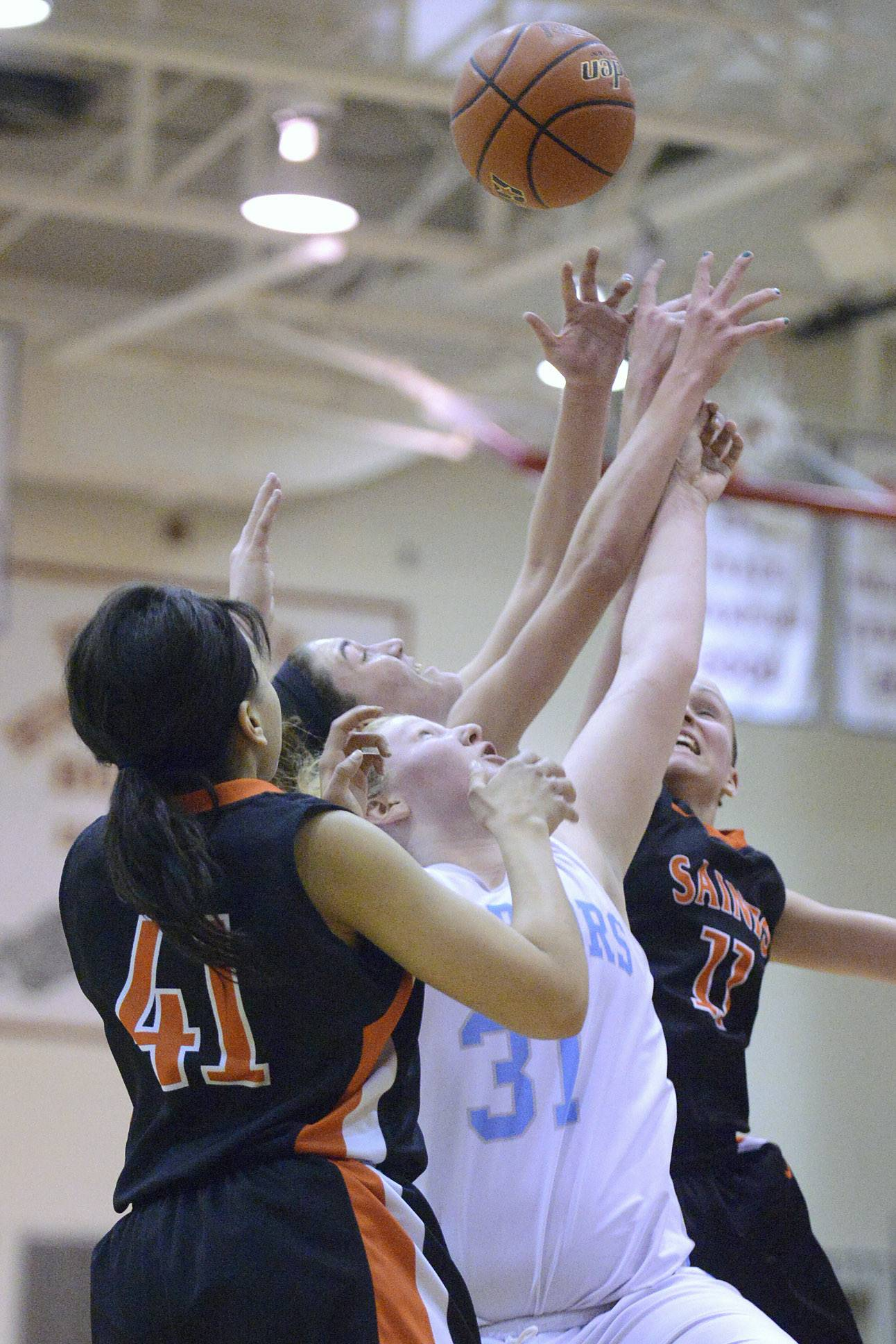 St. Charles East's Keyana Williams (41) and Katelyn Claussner (11) scramble with Willowbrook's Josie Zabran (31) and Molly Krawczykowski (back) for a rebound in the second quarter on Tuesday, February 18.
