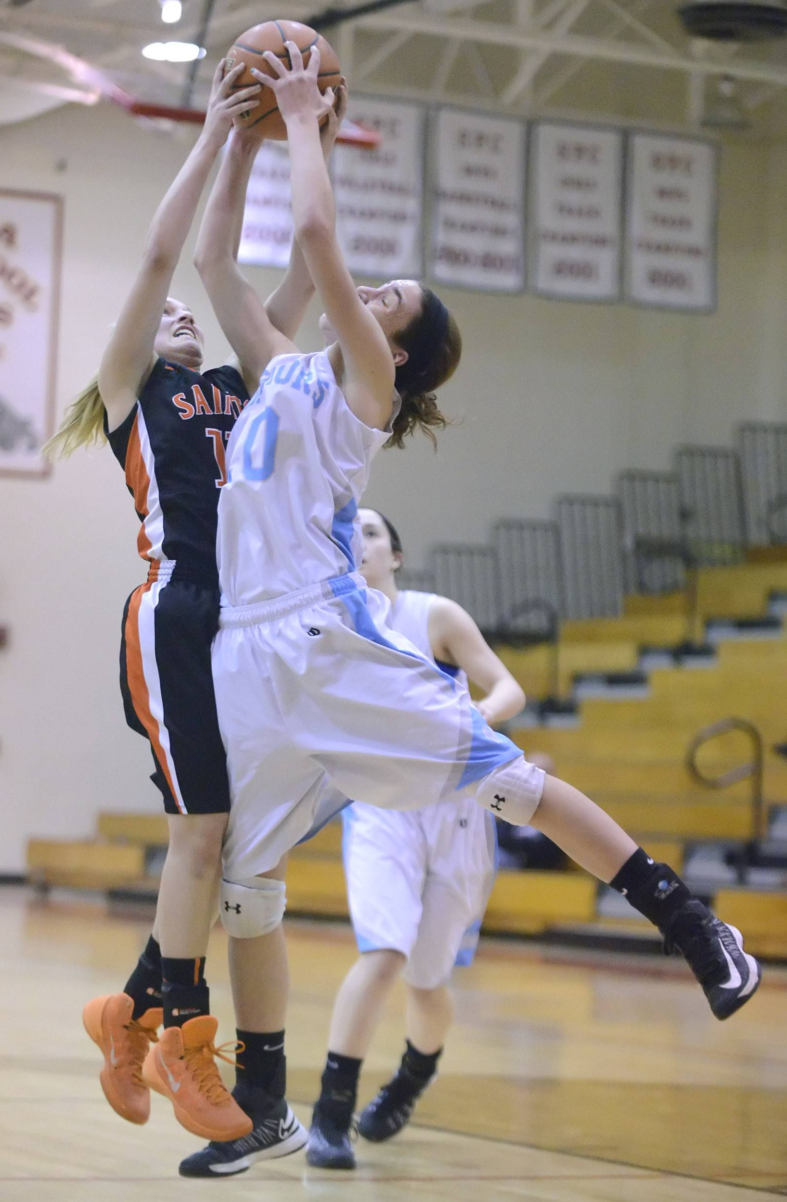 St. Charles East's Katelyn Claussner and Willowbrook's Molly Krawczykowski both leap for a rebound in the second quarter on Tuesday, February 18.