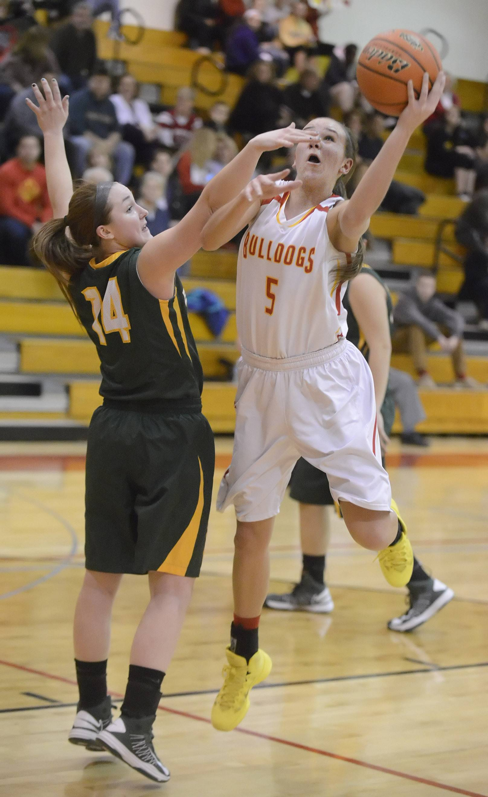 Batavia's Liza Fruendt shoots around a block by Elk Grove's Taylor Brown in the first quarter on Tuesday, February 18.