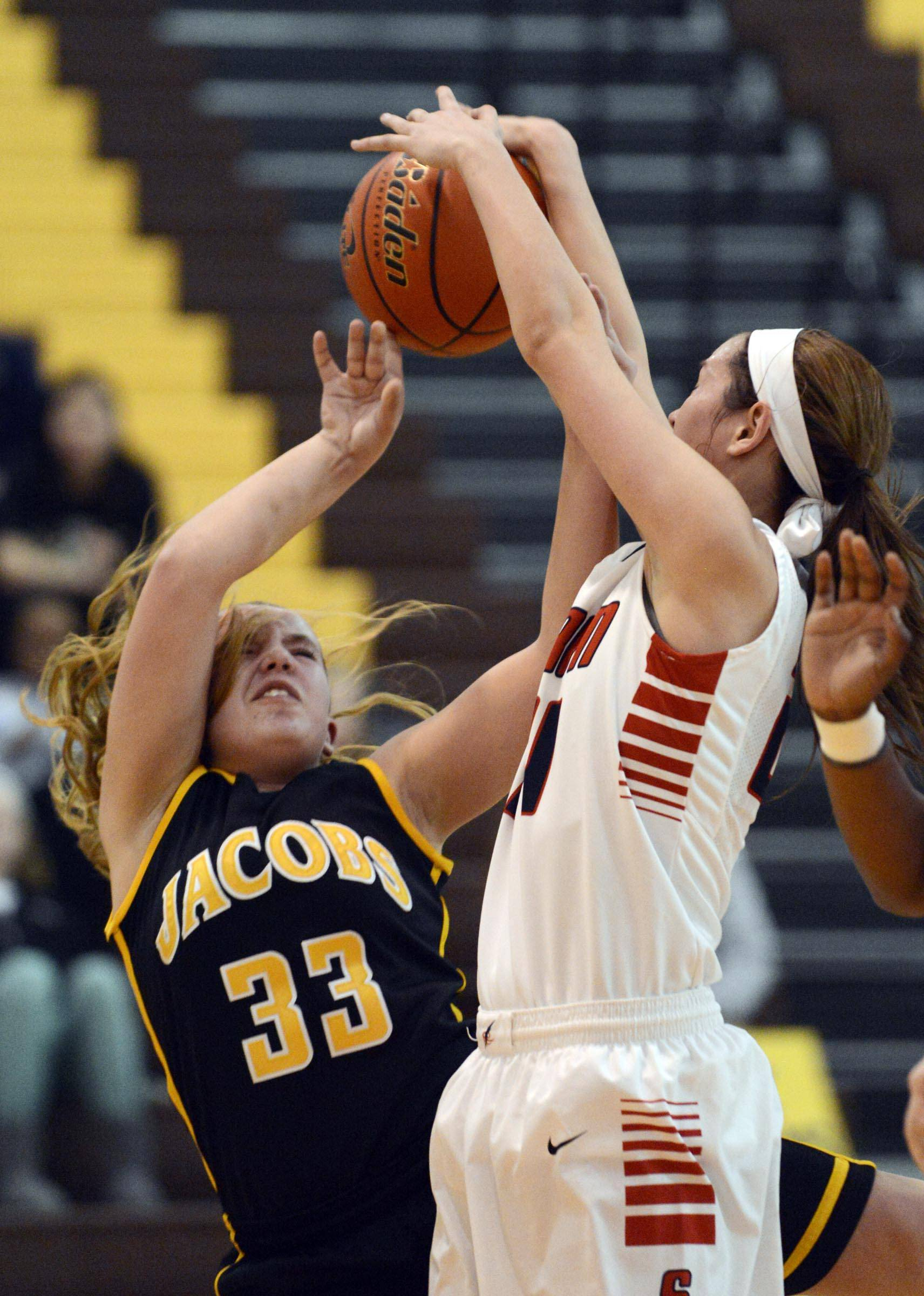South Elgin's Kennede Miller blocks a shot by Jacobs' Jessica Powell Tuesday in a Regional semifinal game in Algonquin.