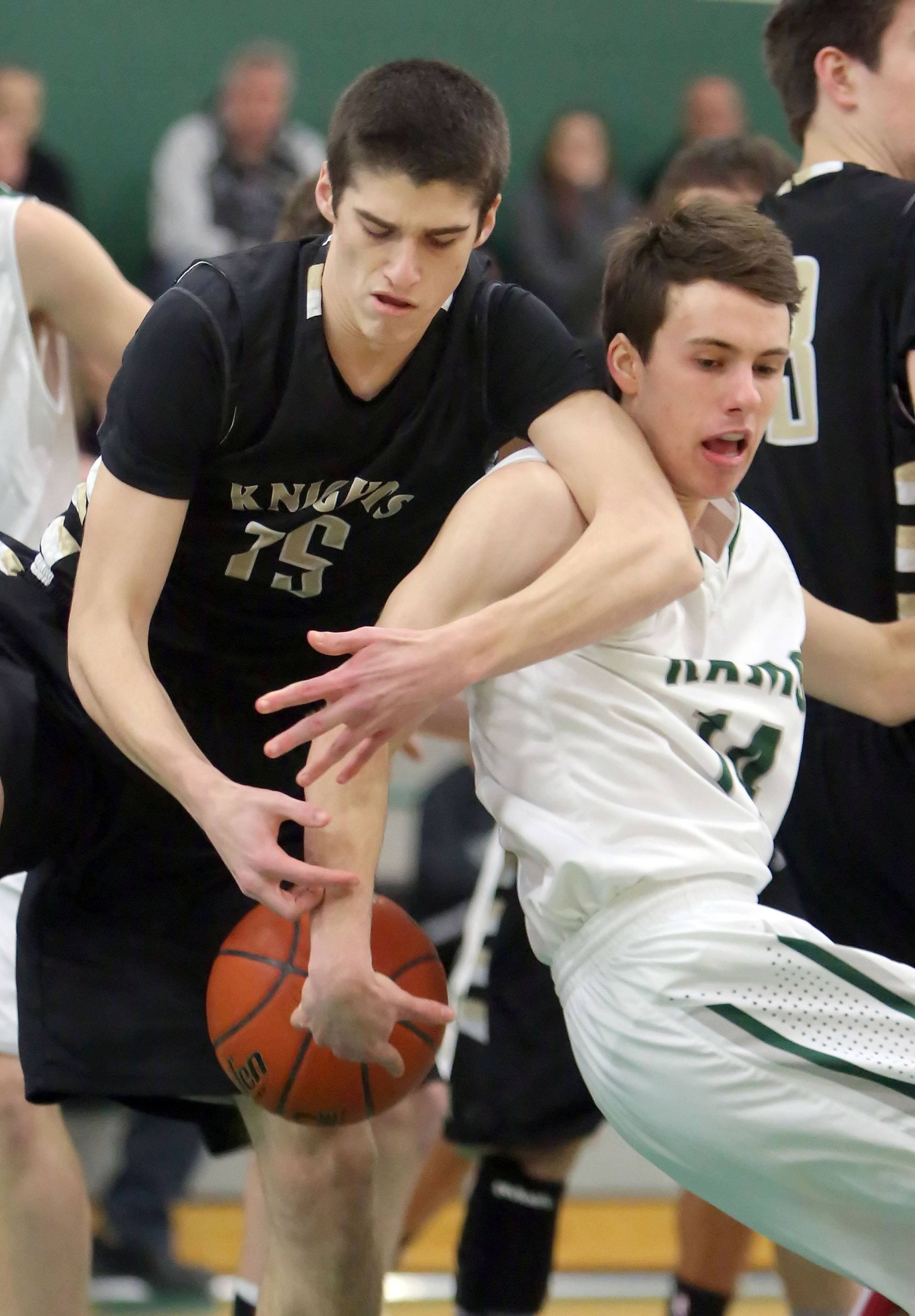 Grayslake North's Dom DiProva, left, and Grayslake Central's Charlie Anderson scramble for a rebound on Tuesday night at Grayslake Central.