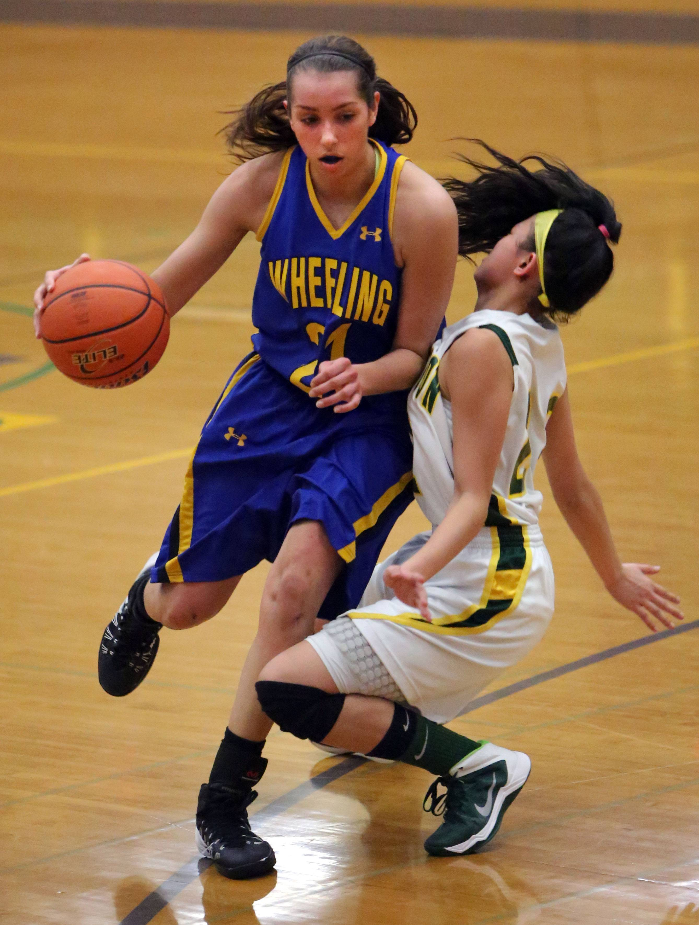 Wheeling's Deanna Kuzmanic, left, drives into Stevenson's Janine Fajardo during Class 4A regional semifinal play at Waukegan on Wednesday.