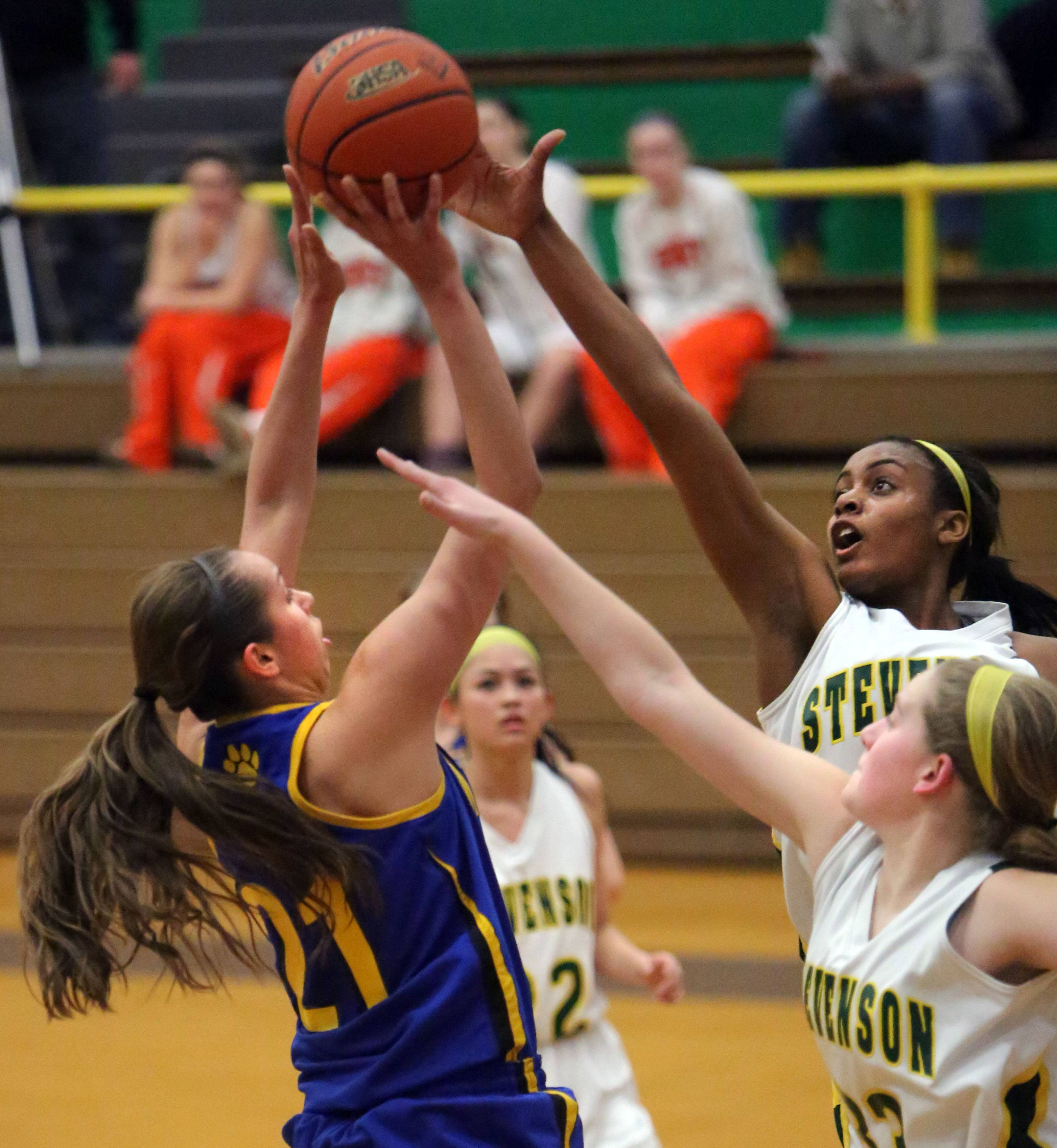 Wheeling's Deanna Kuzmanic, left, tries to shoot over Stevenson's Taylor Buford during Class 4A regional semifinal play at Waukegan on Wednesday.