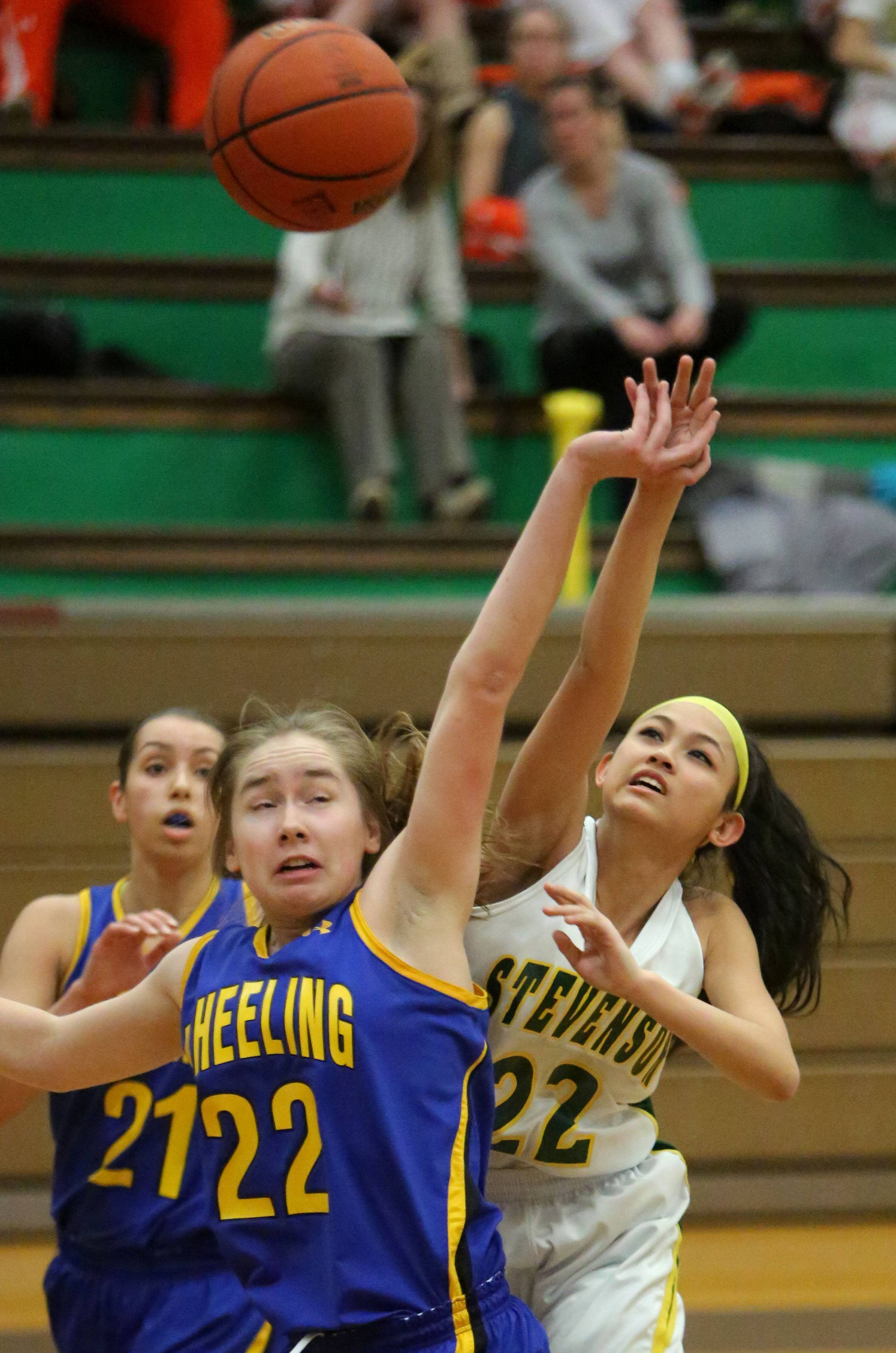 Wheeling's Hailey Dammeier, left, and Stevenson's Janine Fajardo stretch for a rebound during Class 4A regional semifinal play at Waukegan on Wednesday.