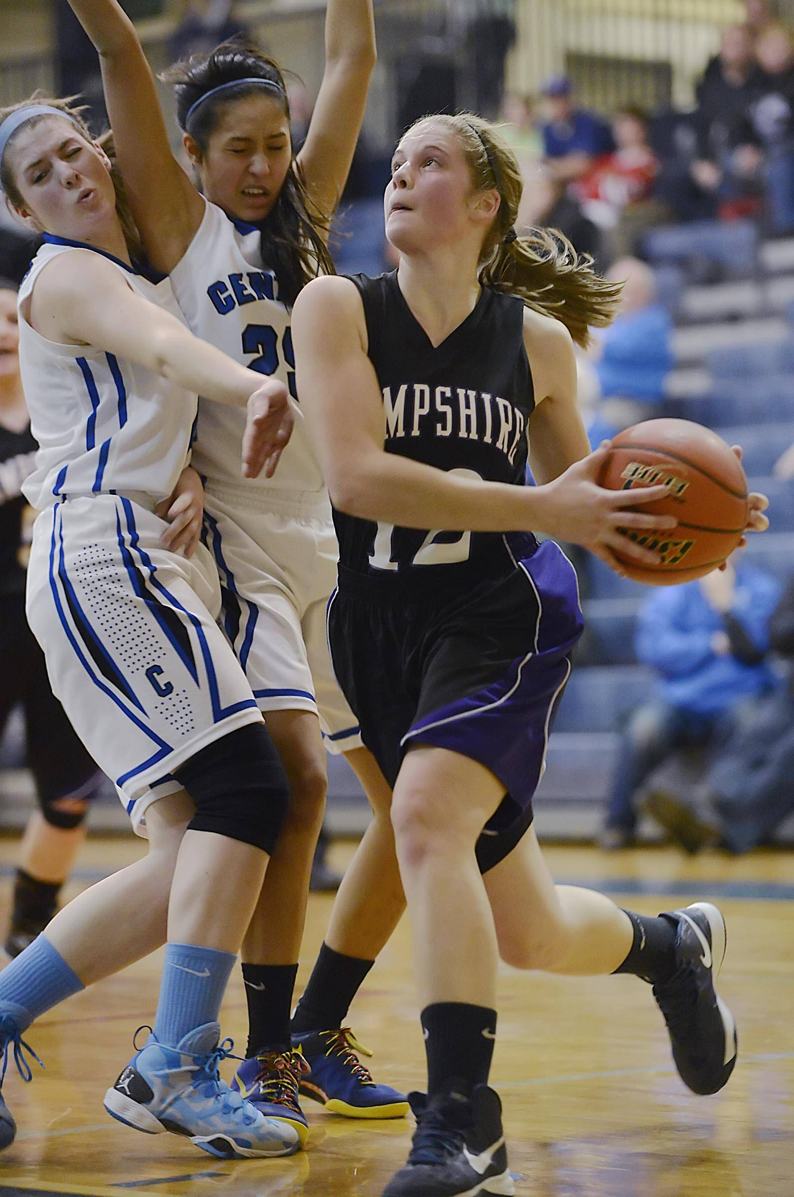Burlington Central's Kayla Ross and Samantha Cruz collide as Hampshire's Nikki Dumoulin drives to the hoop.